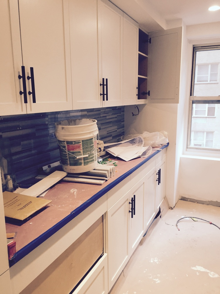 Nyc kitchen, black and white scheme, black cabinet hardware, white shaker cabinets, marble backsplash