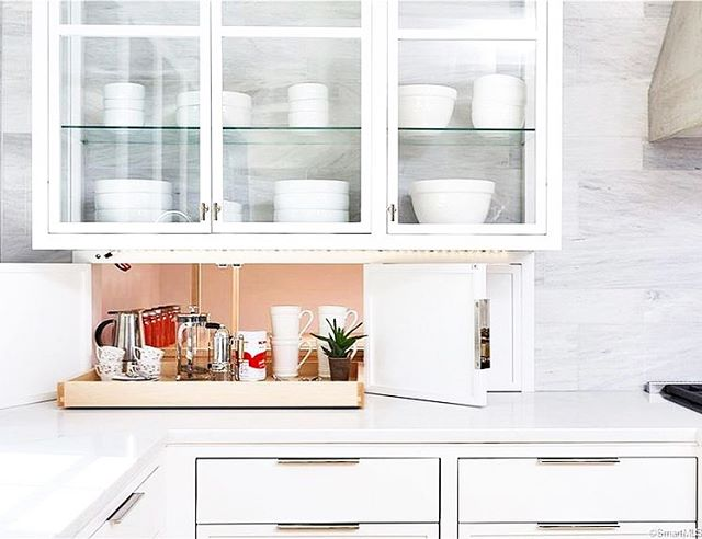 The coolest organization ever happened in this kitchen and the pantry has direct access from next to the range Thru these cool doors. How convenient right?!! #allie_wood_design_studio #newconstruction #trimdesign #modernkitchen #whitekitchen #skalatile #glasscabinets