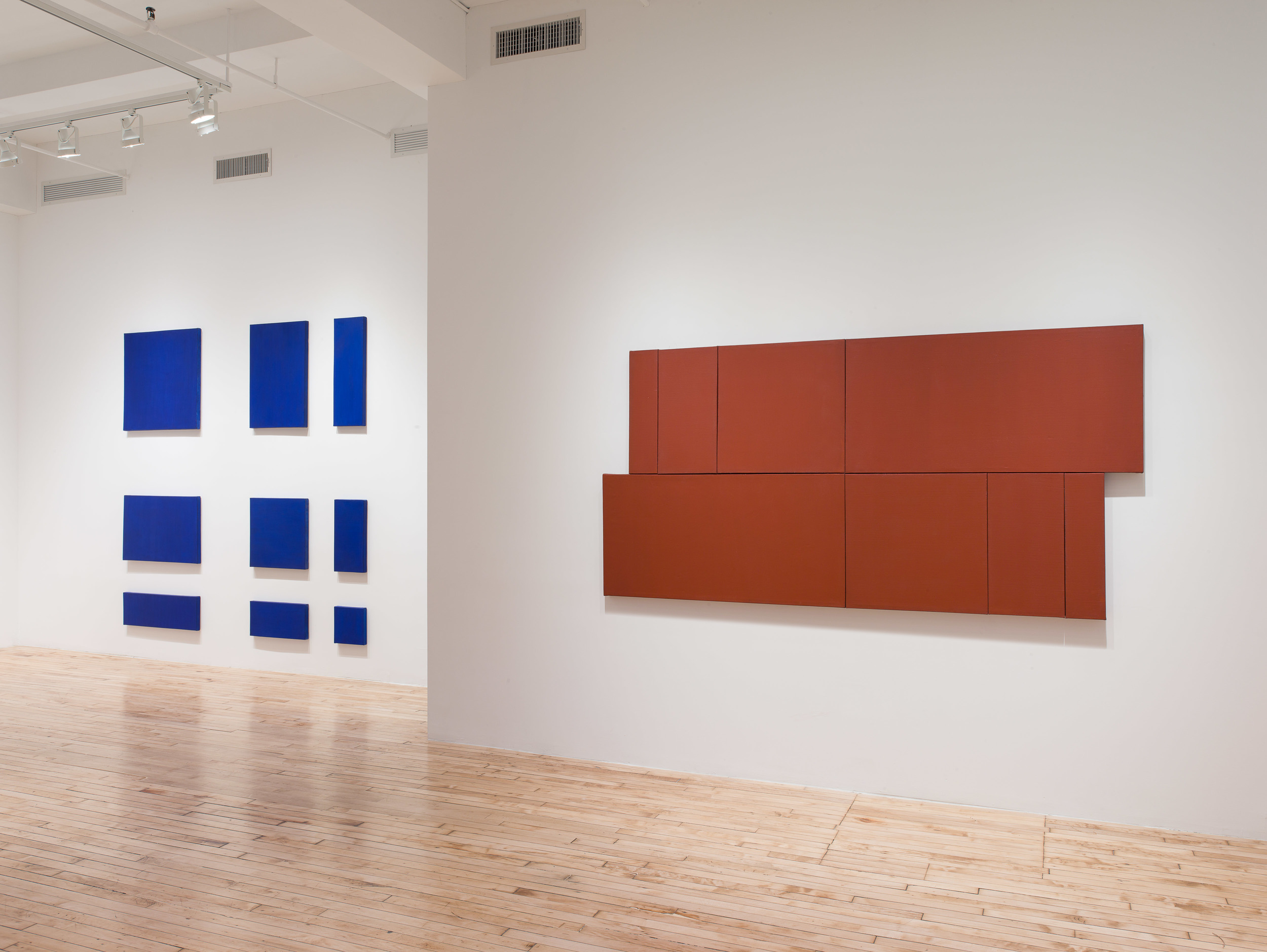 Grid of blue rectangles on the far wall of the gallery.  Long rust colored canvases hang on the wall in the foreground.