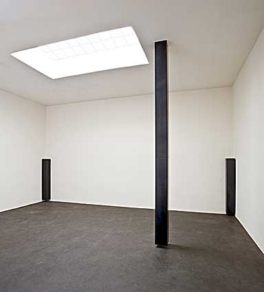 Three floating columns of graphite in a white room. The two in the corners are half the height of the wall and the one in the center hangs from the ceiling to just above the floor.