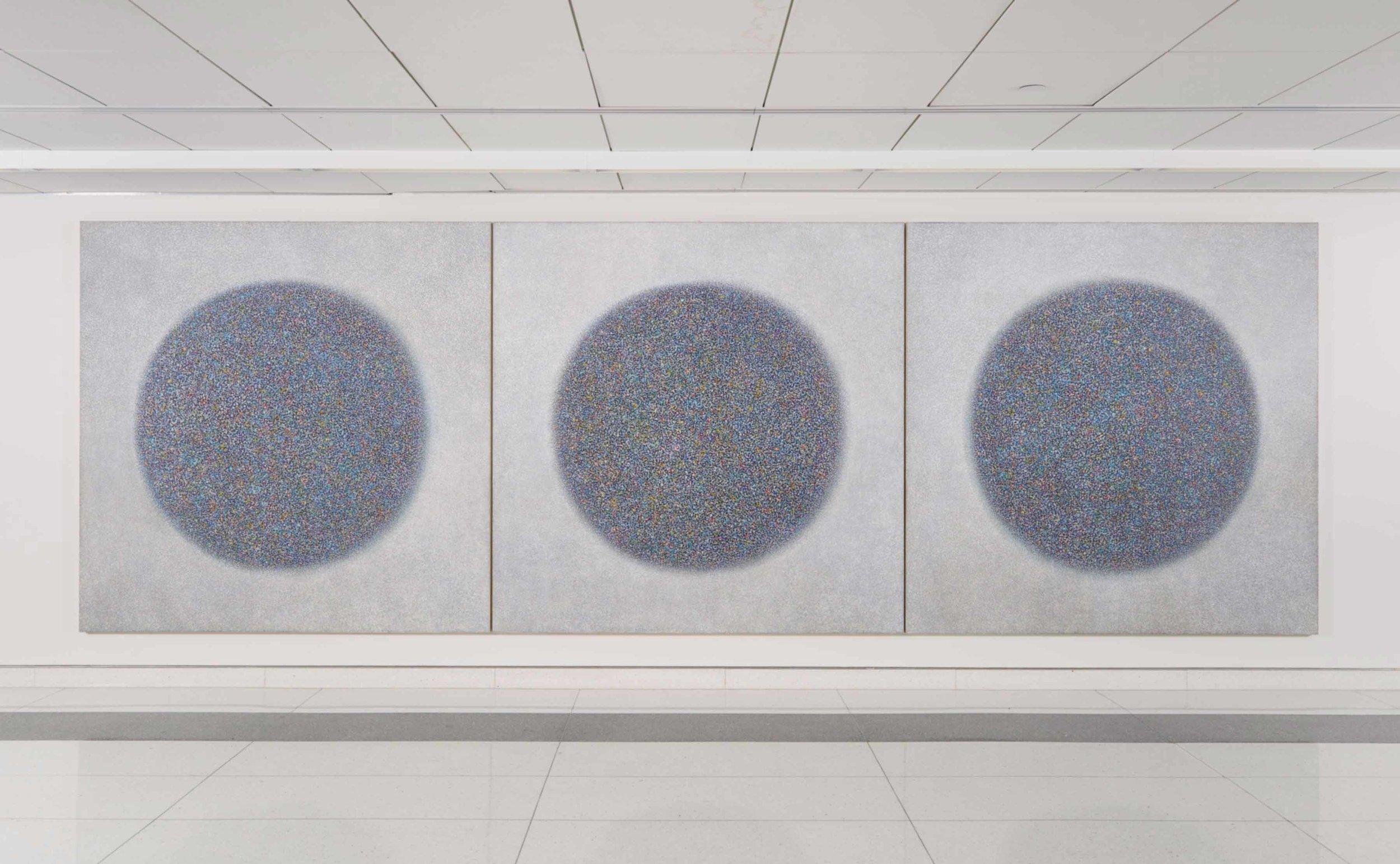 Triptych of three mainly blue circles in a pointillism style on a white background.