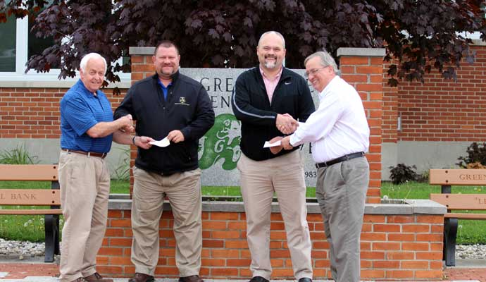 PHOTO CAPTION:Dick Brown (left) and Keith Foutz (right) give donations to Dave Ernst and Aaron Shaffer. (Gaylen Blosser photo)
