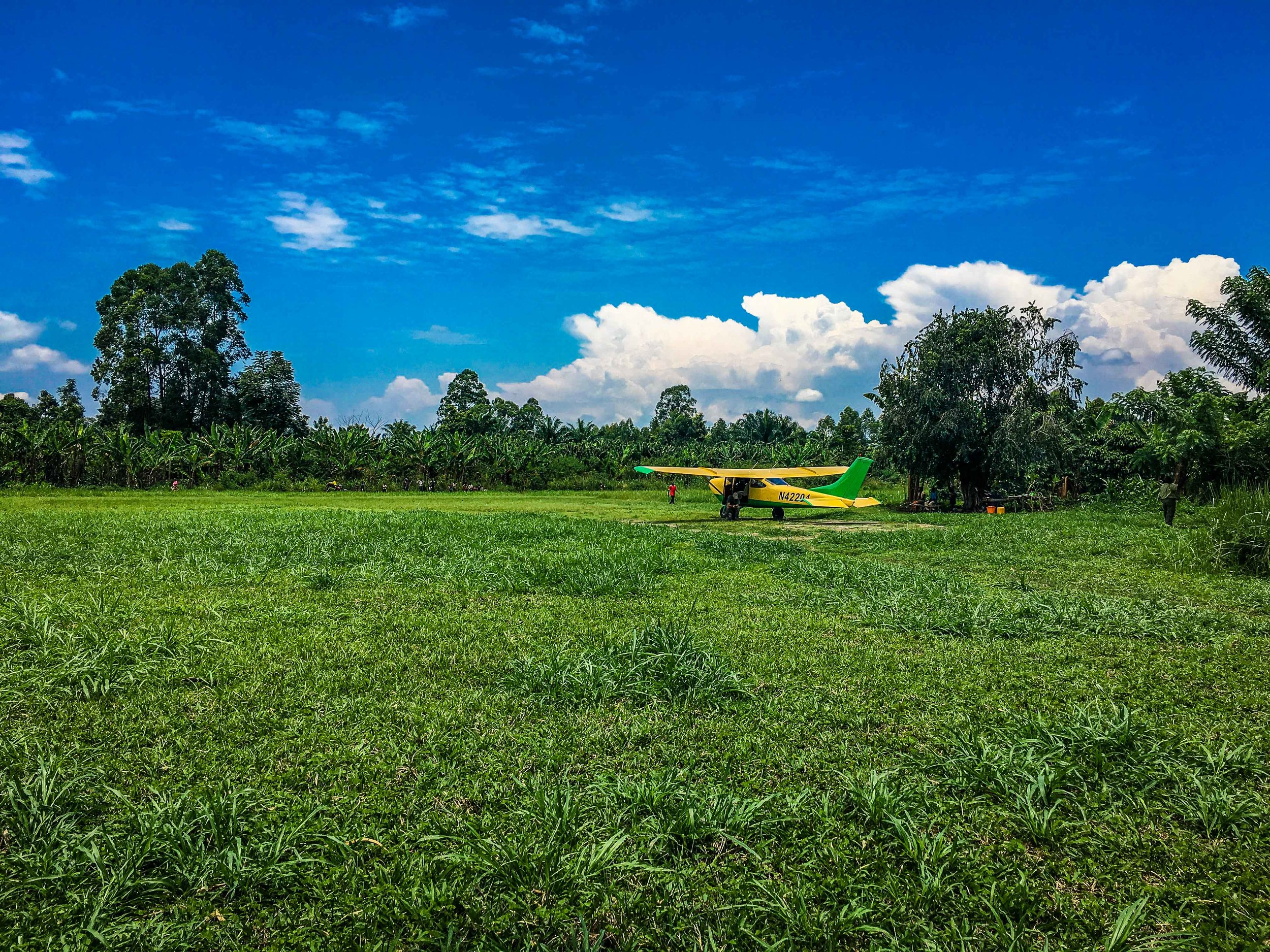 "Runway at the base of the Rwenzori Mountains. Farmers stood along the runway waving. The ""FBO"" is there under the tree ;)"