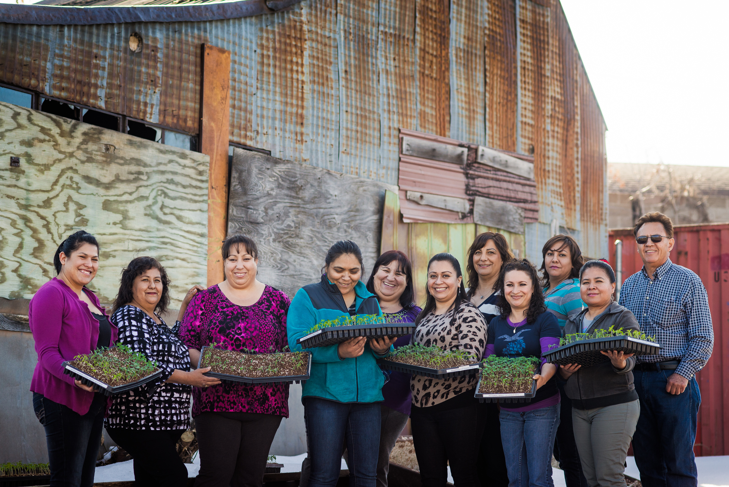 Promotoras with their children in front of the old greenhouse site, Promotoras as a group, Promotoras with seedlings for the 2015 Revision gardens, a final staged image taken in the Revision kitchens with the Promotoras to show the power of La Cocina and the cooking classes.