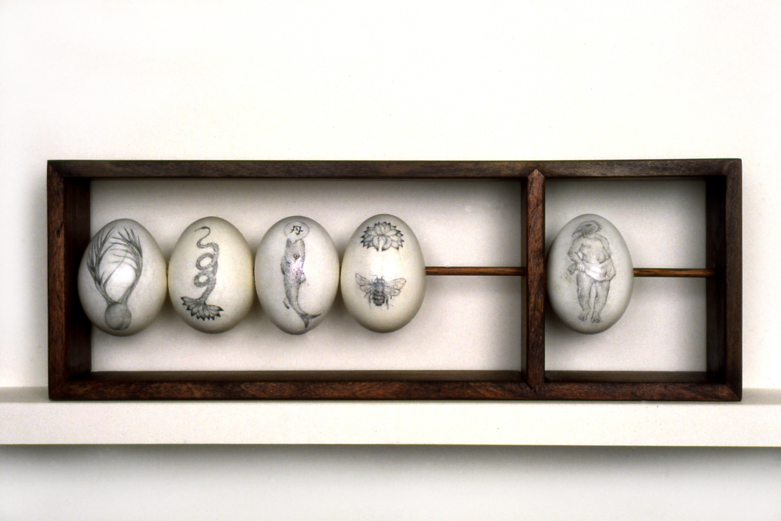 "ABACUS The  egg ""beads"" on this one-row abacus are embellished with graphite drawings of hybrid transformational symbols from various cultures, suggesting an alternative approach to mathematical certainty."