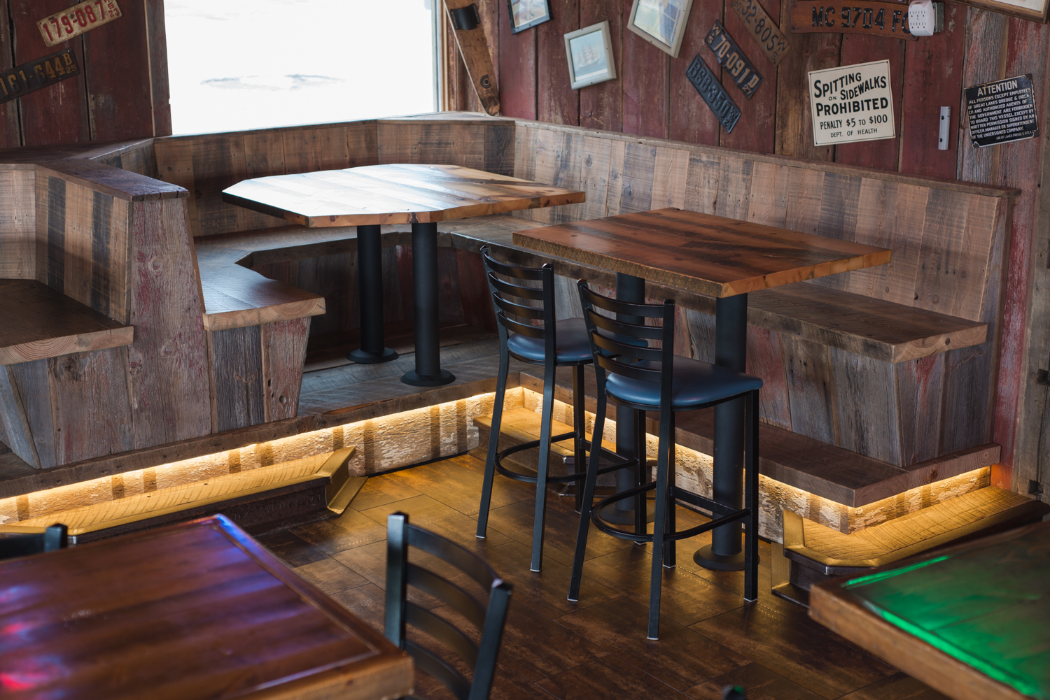 Rail step up to a corner booth creates height enough to match the pub tables.