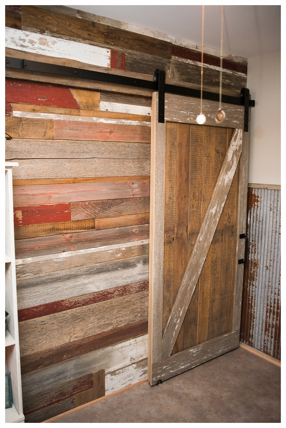 A sliding custom barn door rests against a rich patchwork of different barn wood planks.