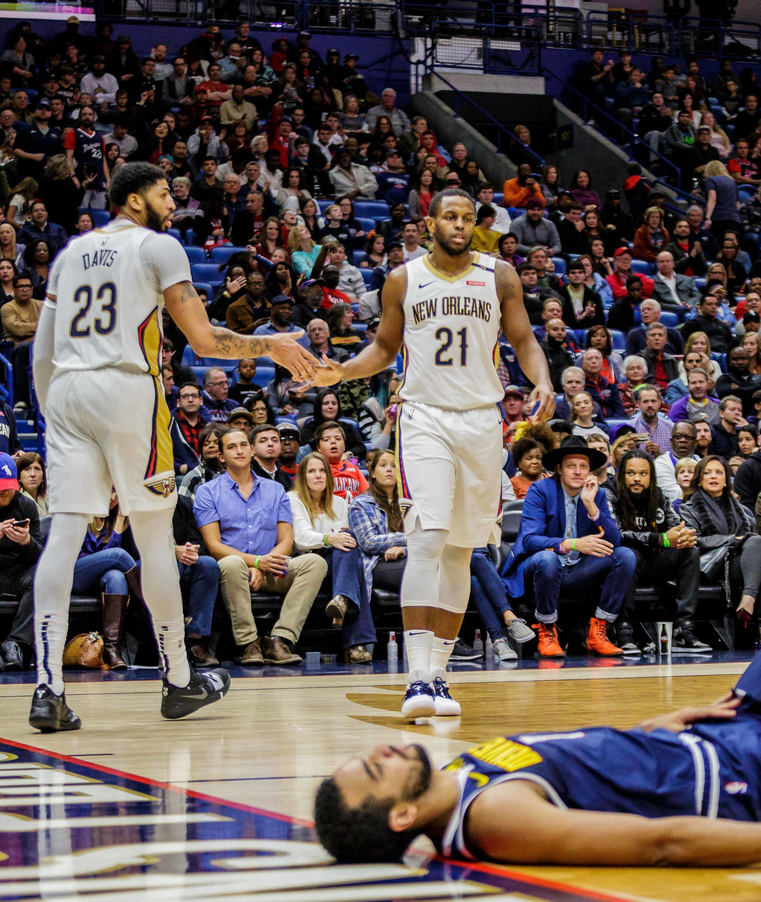 Denver Nuggets forward Trey Lyles (7) lays on the floor after unsuccessfully defending New OrleansPelicansforward Anthony Davis (23) who shakes hands with Darius Miller (21) during the second half of an NBA basketball game in the Smoothie King Center in New Orleans, La. Monday, Nov. 17, 2018. ThePelicanswon, 125-115.
