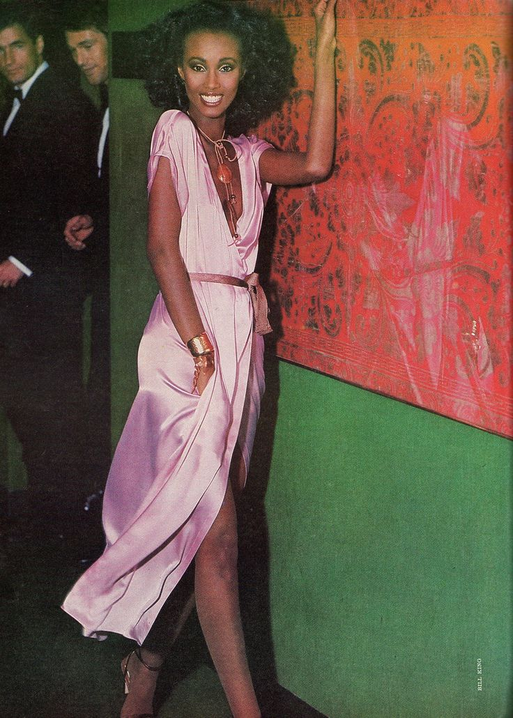 Photo of Supermodel Iman in 1978 wearing a solid pink DVF inspired wrap dress by Calvin Klein