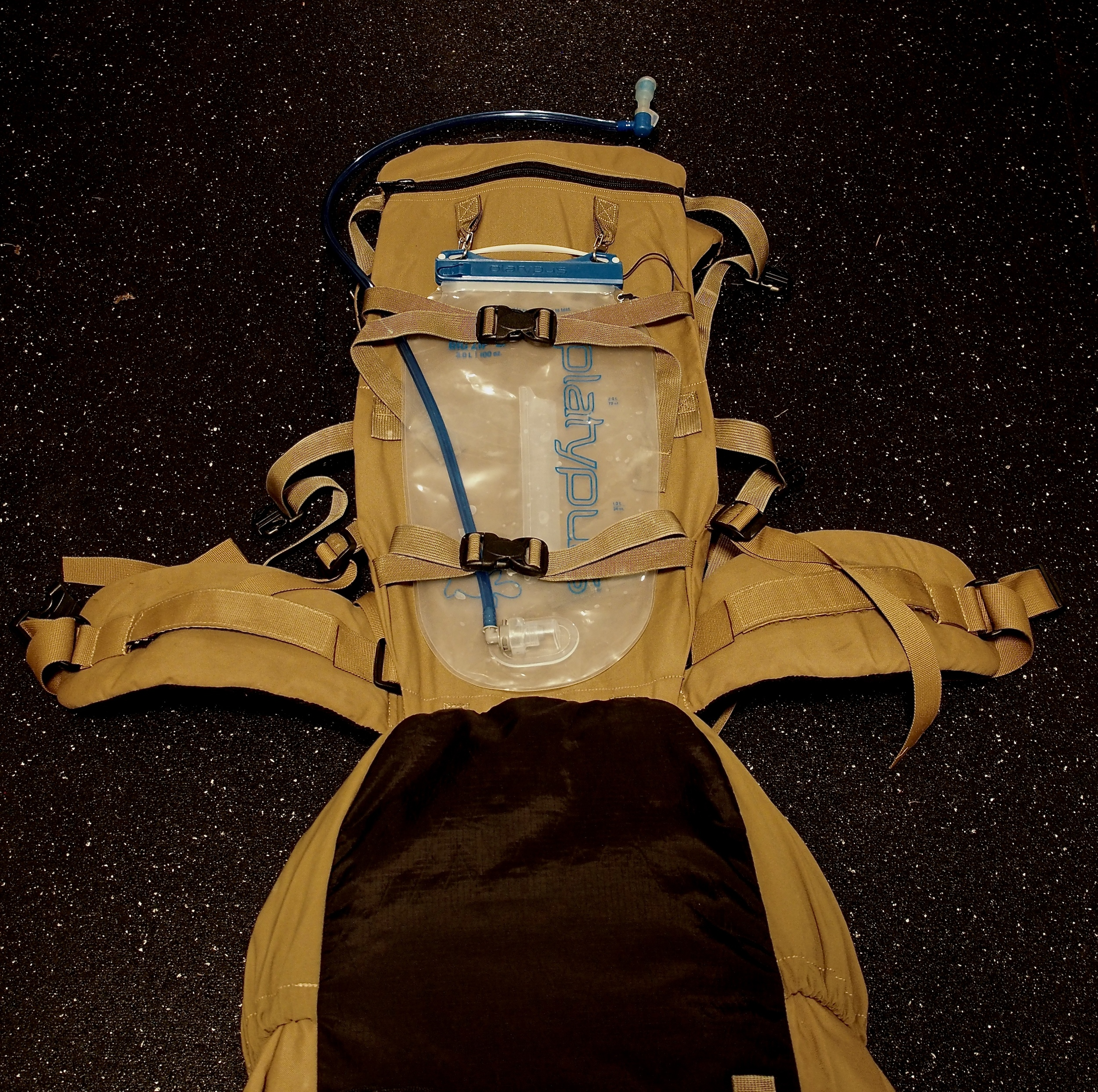Here's a picture of my bladder system. I've bounced between canteens, bottles, and bladders, but until I found this Platypus bladder, it was all a pain in the neck. This bladder has structure, has a zip-top closer making it easy to clean, and is durable. My Exo Mountain Gear pack allows me to sandwich the bladder between the bag and the frame so I don't take up valuable real estate inside the pack. This also keeps the water weight as close to my back as possible.