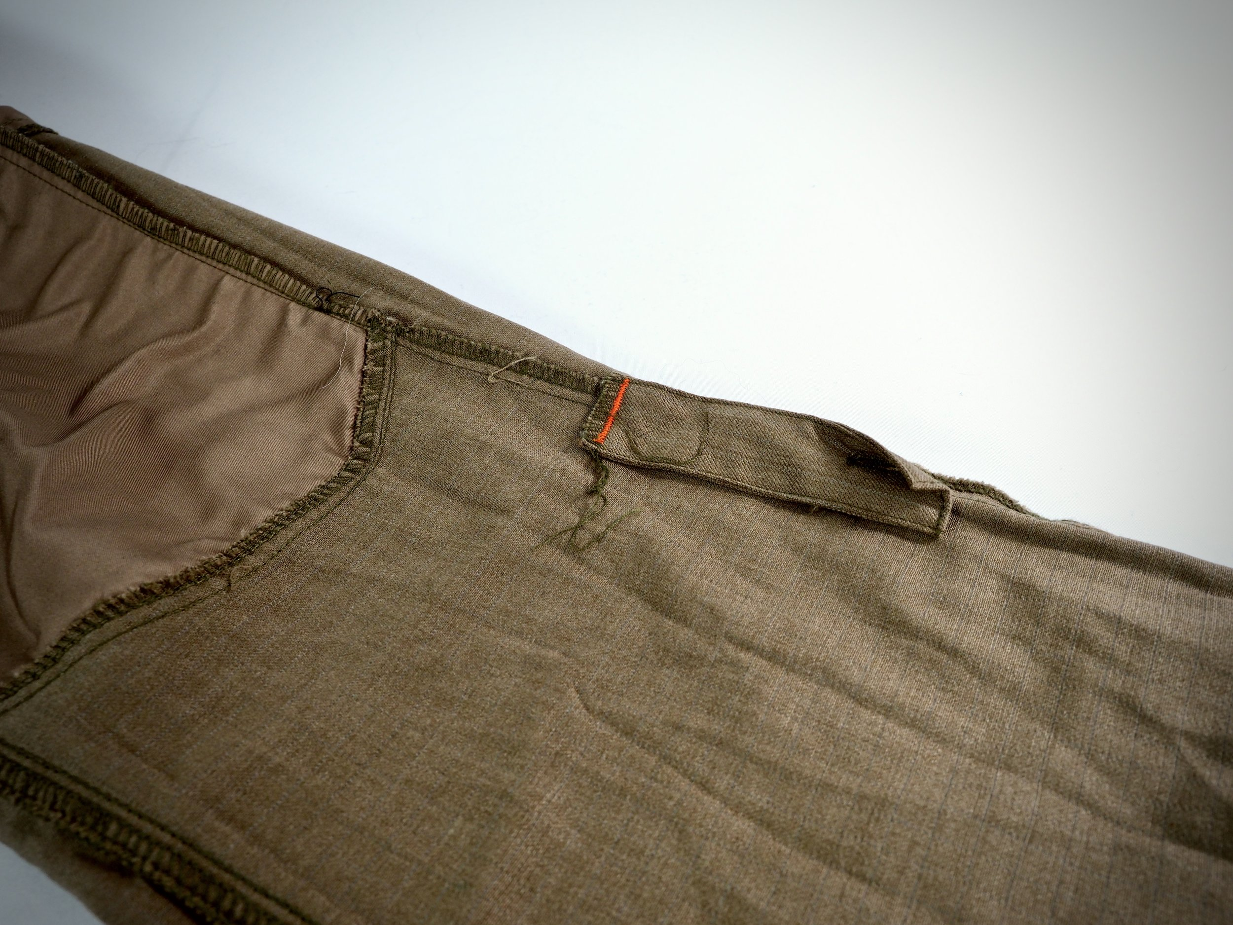 This little bit of fabric is for you to use when you roll up the pants. You can use a button on the outside of the pant to secure them.