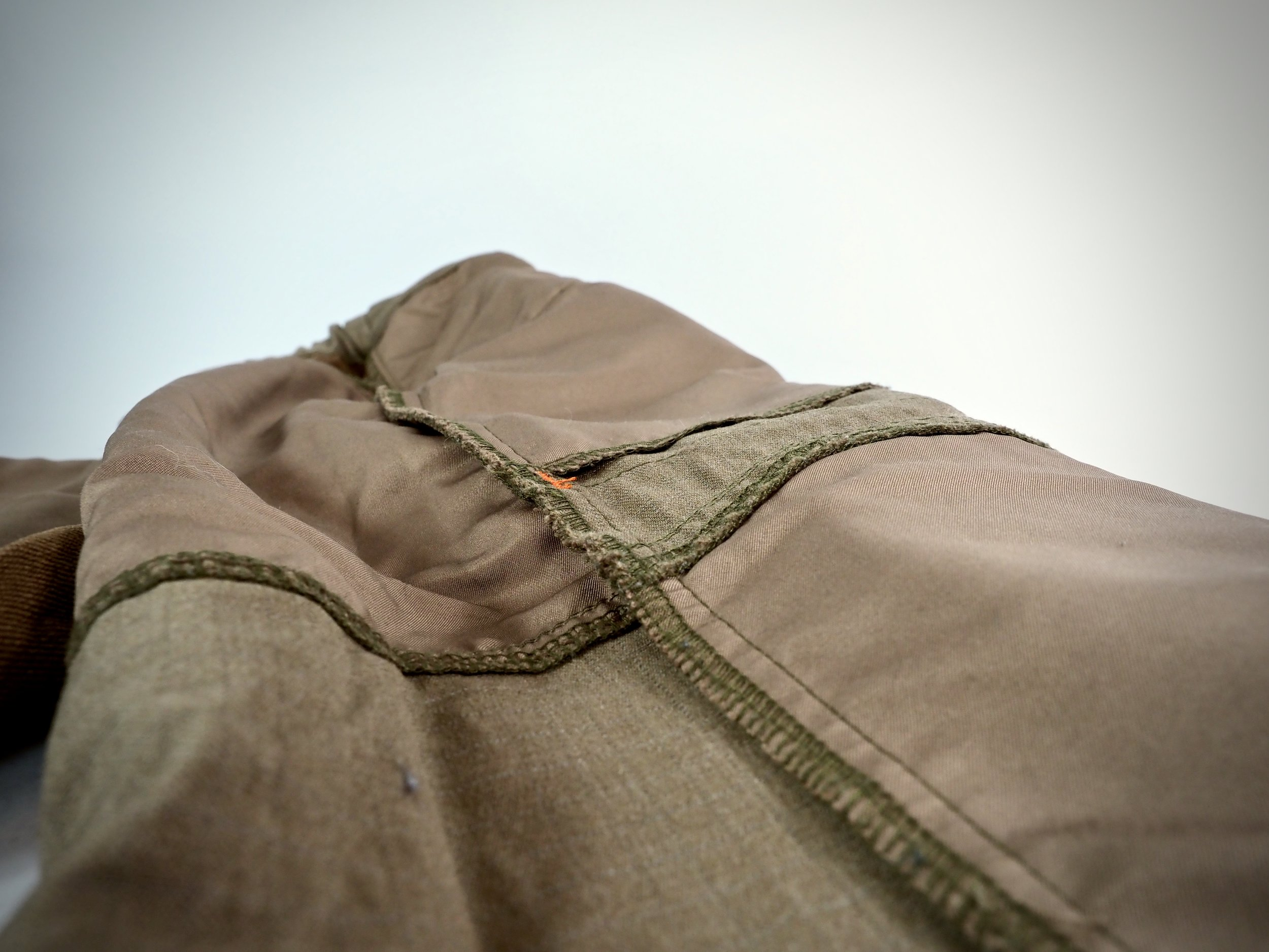 The stitching of the long vertical seam along the outside of the leg.