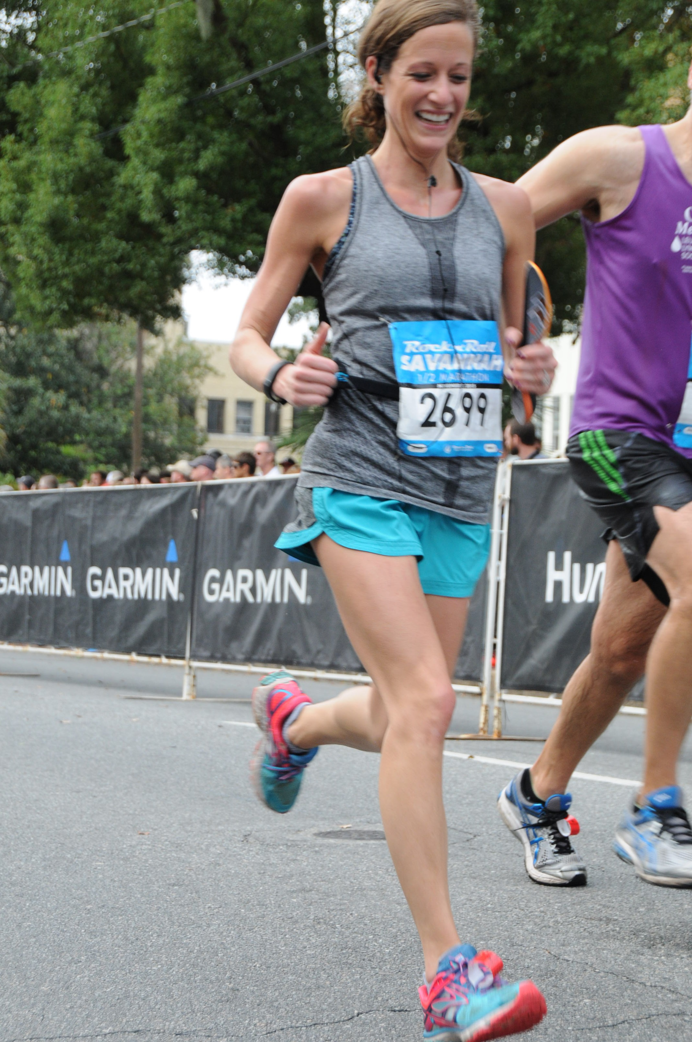 ***This was towards the finish line in Savannah where I met a new friend to compete against across the finish line. Also, that is my insole in my left hand that I had to take out at mile 6 because it had given me a blister the size of an egg. The moral of that story is don't buy new insoles or shoes at the Expo, stick to what you already have.