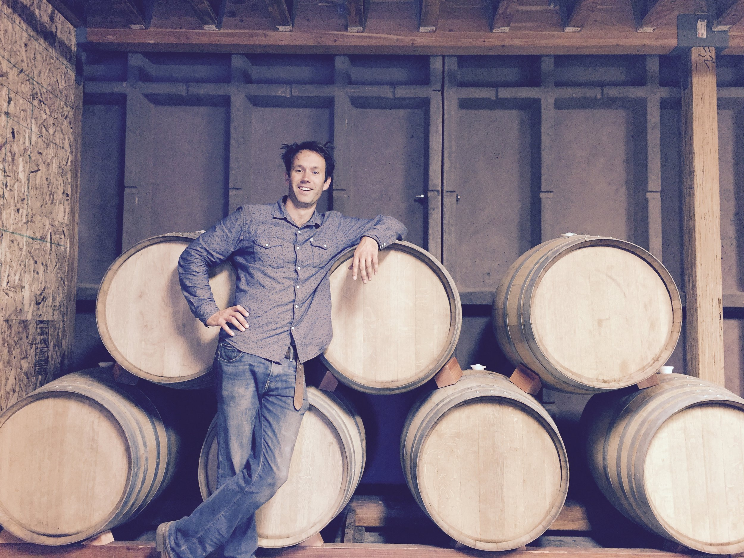 dylan in front of barrels.jpg
