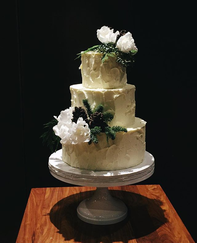 The mix of fresh greenery, sugar roses and chocolate pine cones on this @districtwineryweddings cake is putting me in a solstice mood.