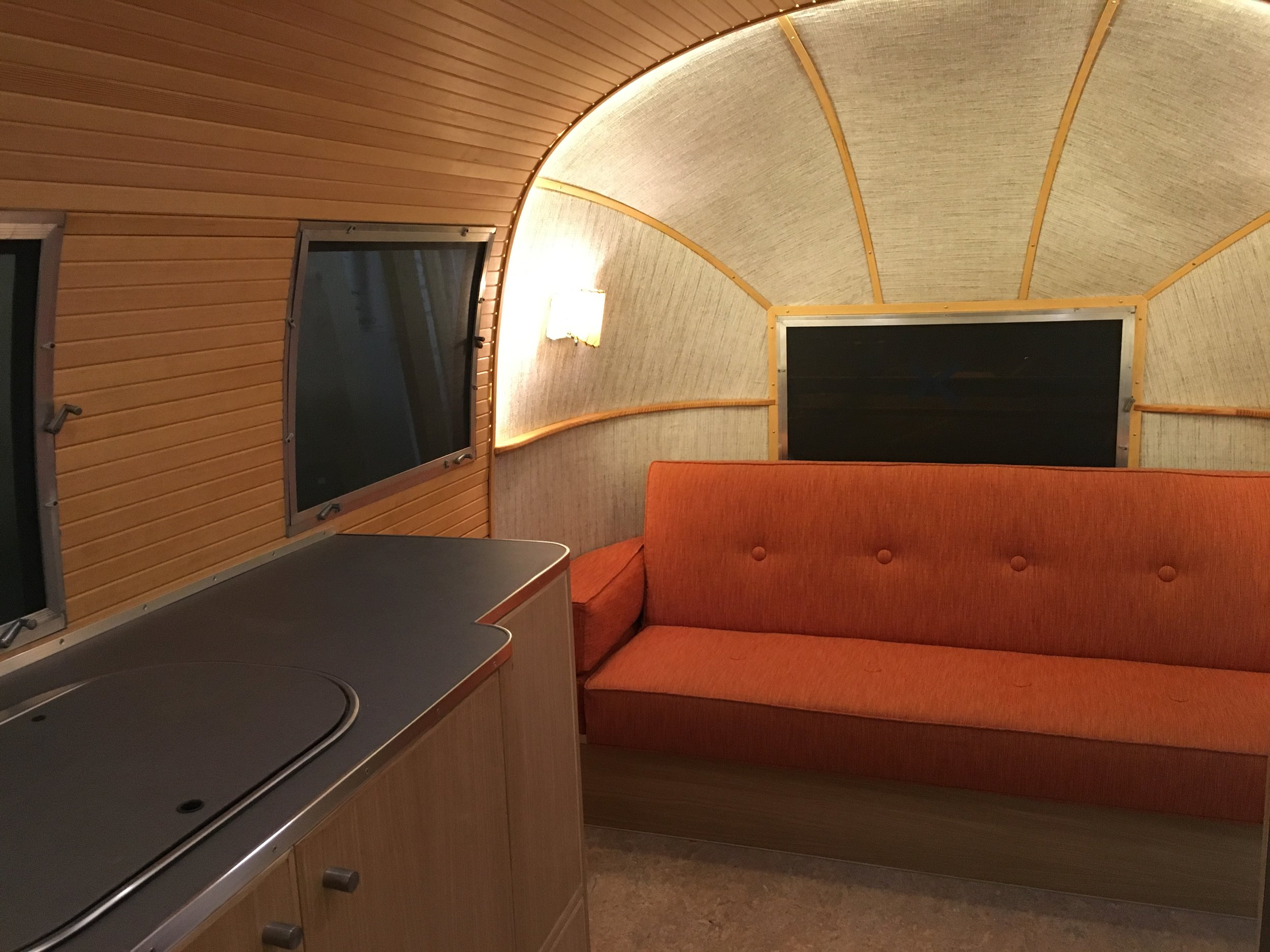 Upholstered end caps and straight-grain tongue and groove Douglas fir wraparound ceiling and walls. Custom orange click-clack sofa.
