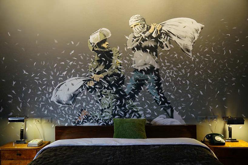 nella camera Bansky un murale dell'artista rappresenta un soldato israeliano e uno palestinese che fanno la battaglia con i cuscini photo via Designboom