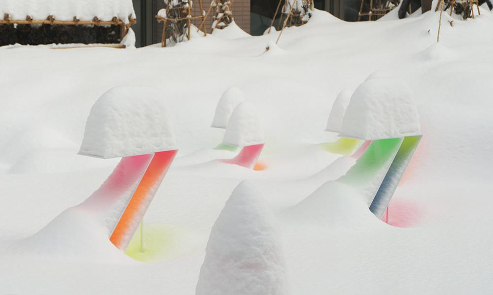 i colori dell'installazione si rifrangono sulla neve con le loro note vivaci e giocose