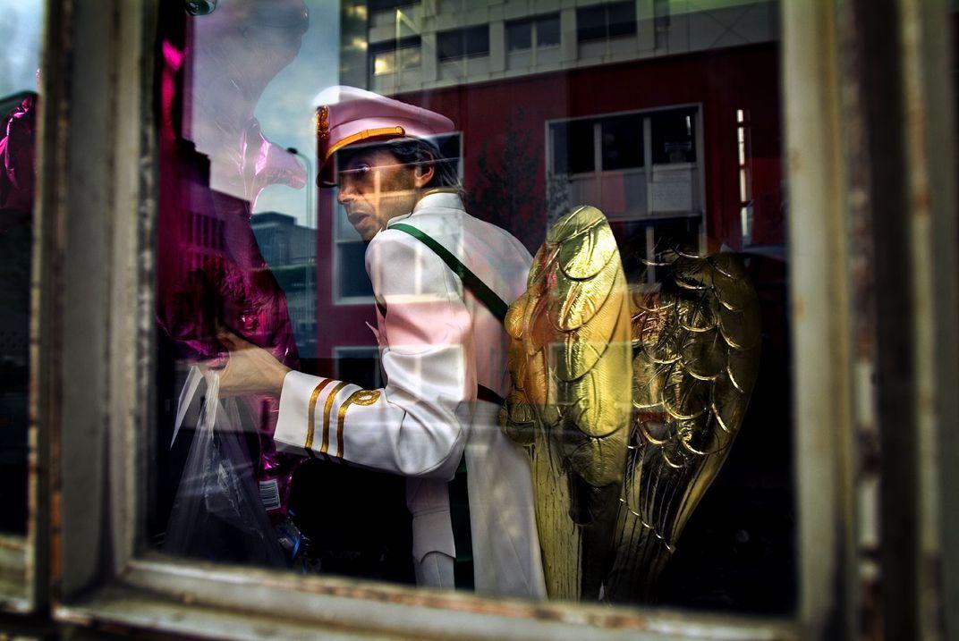 A Belgian Angel, © Alain Schroeder.  Un uomo torna a casa dopo il festival di Mayboom a Bruxelles