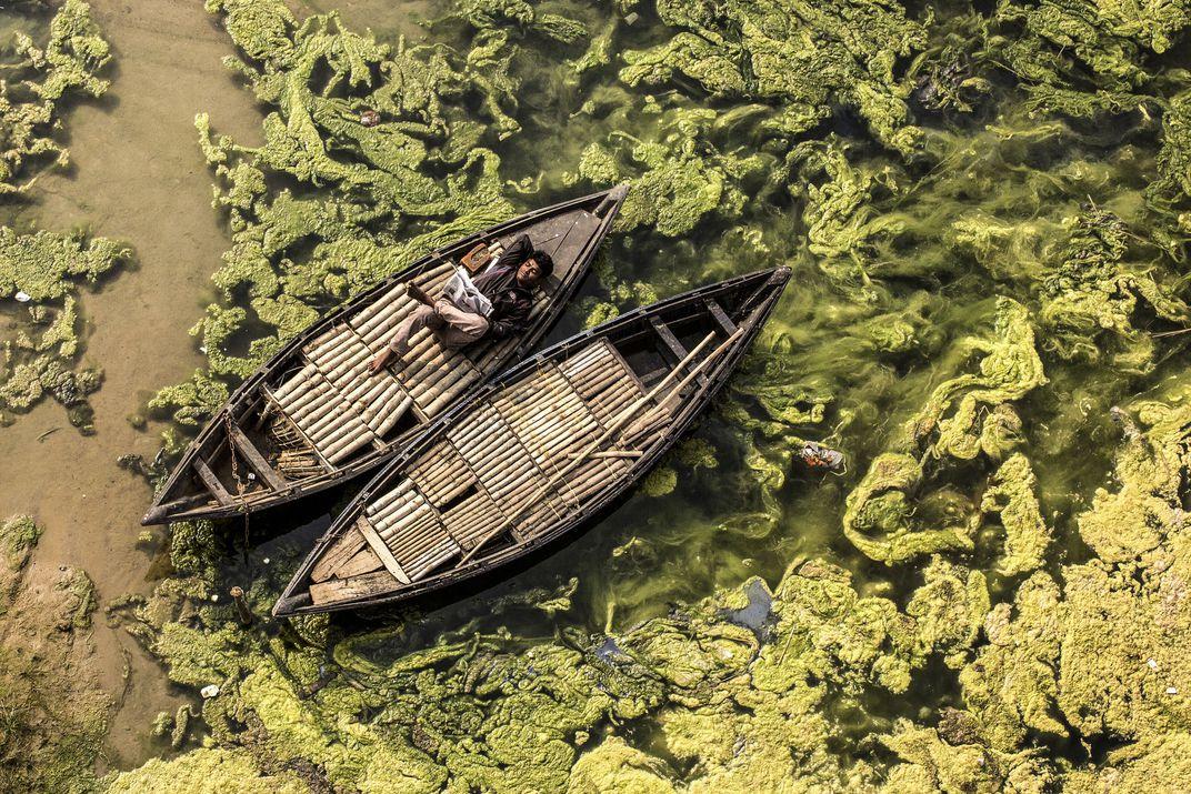 The Boatman, © Debashis Mukherjee.  Un barcaiolo legge un giornale sulla sua barca