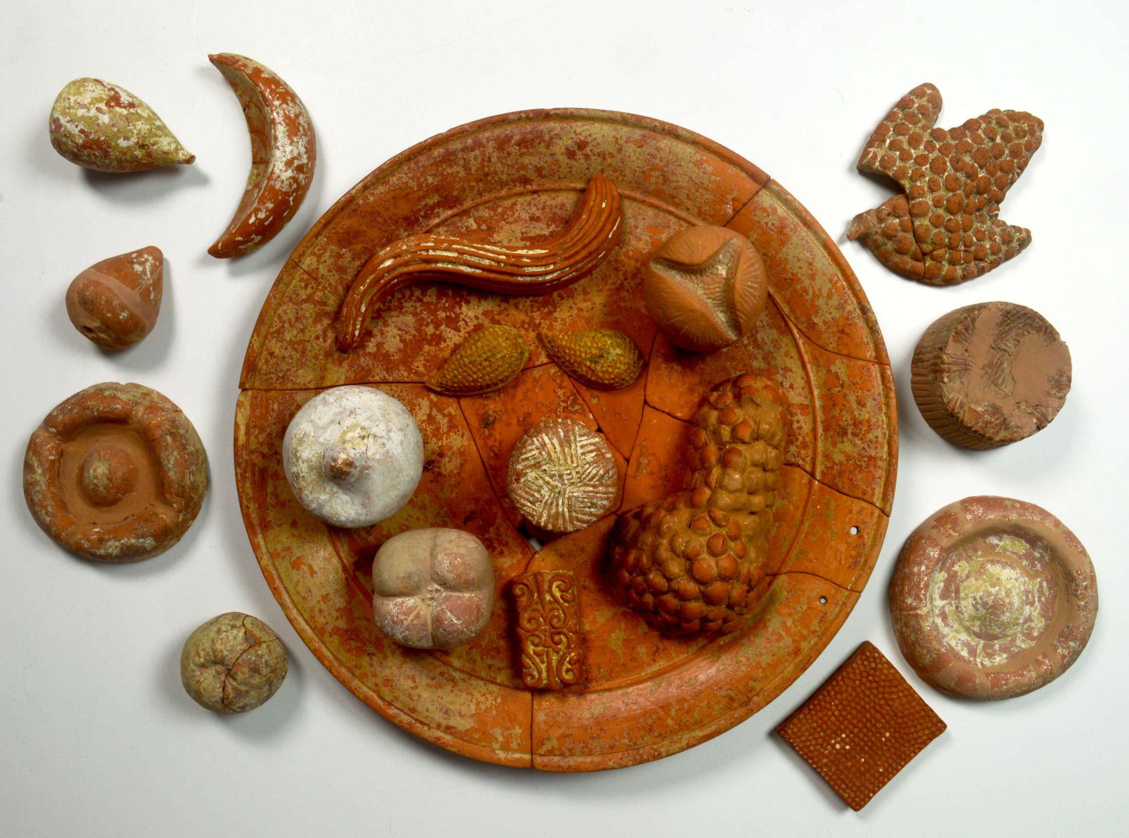 Terracotta votive food: pomegranates (open and closed); grapes; figs; almonds; cheeses; focaccia; honeycomb; mold; long bread, 360 BC. Tomb 11, Contrada Vecchia, Agropoli. Parco Archeologico Di Paestum