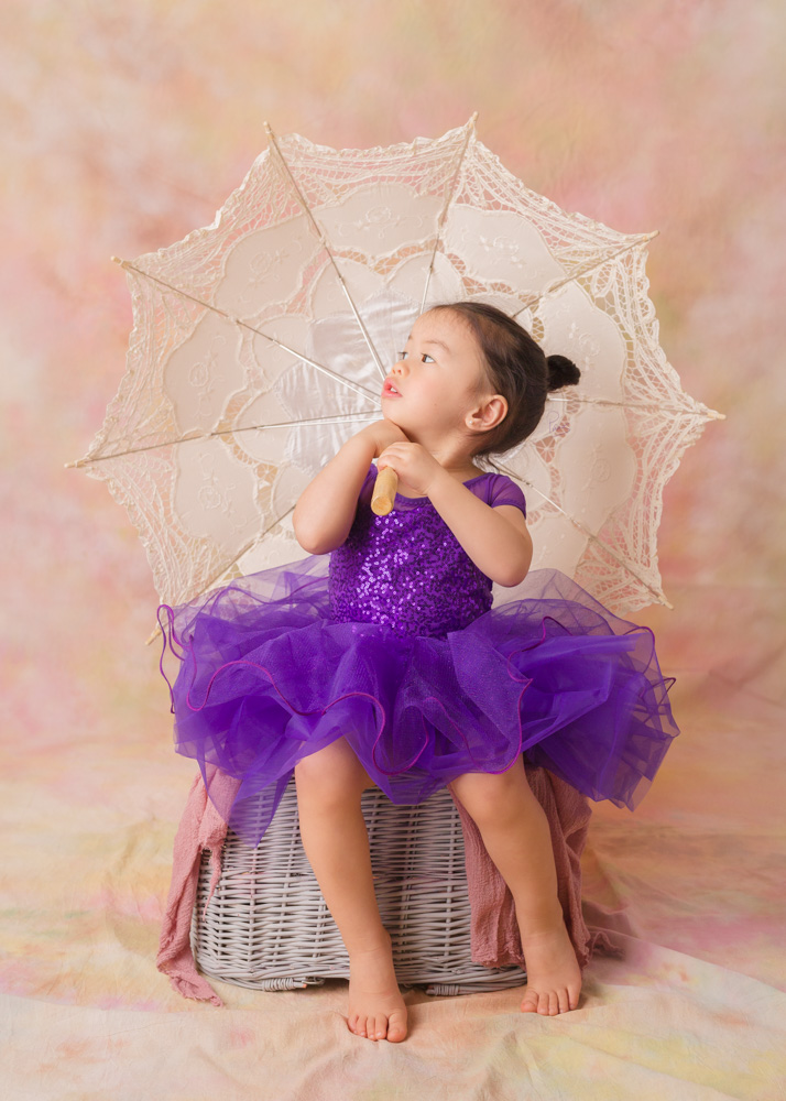 Toddler wearing purple tute holding umbrella. Birthday.