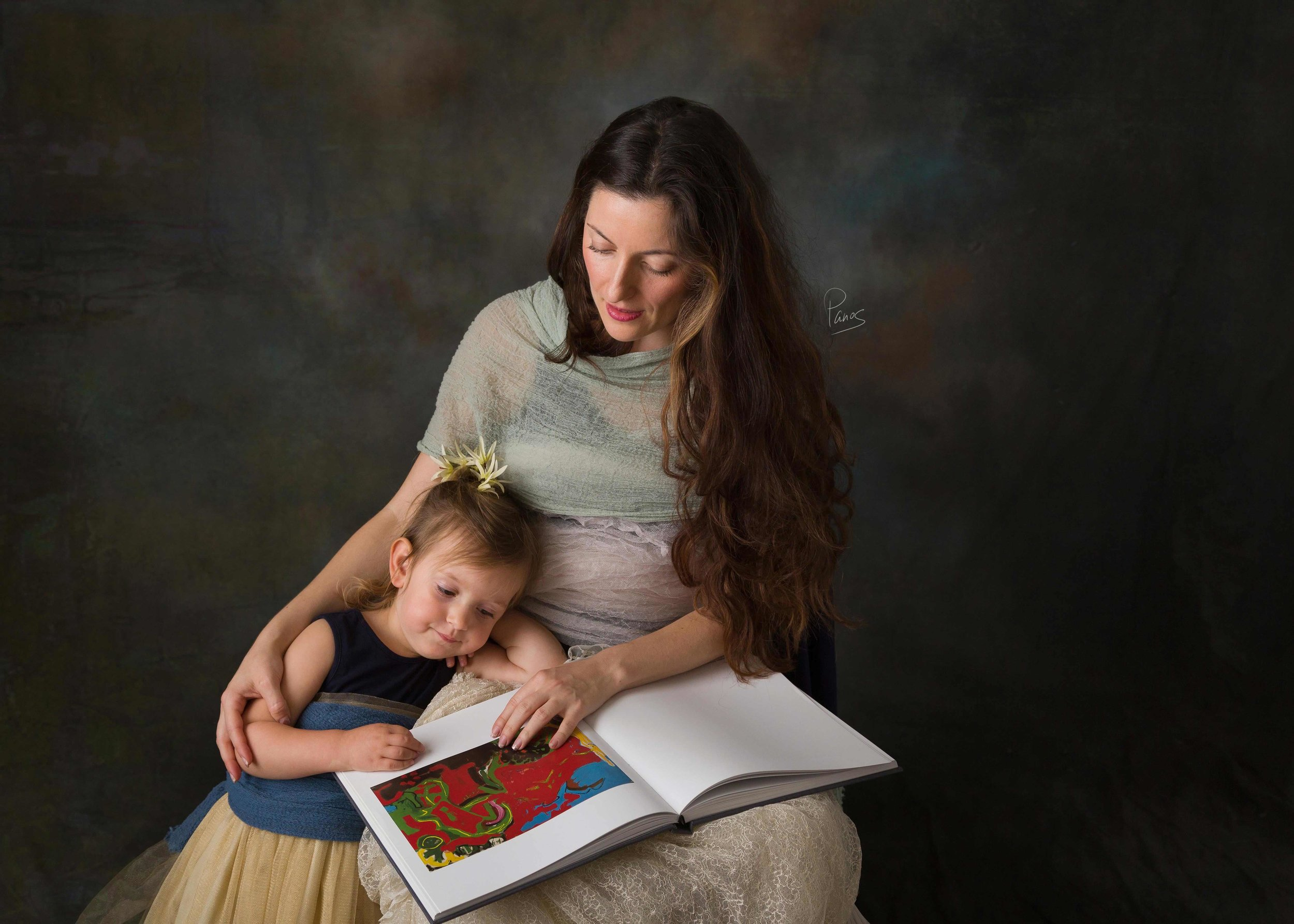 Mother with toddler daughter reading a book.