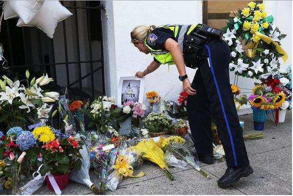 A police officer pays his respects to the murdered victims. Image Source: LA Times