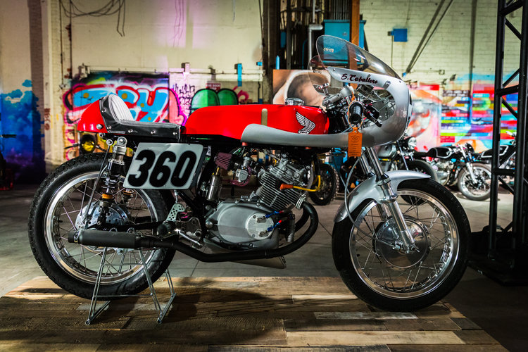 At the Outlier's Guild Moto Show in early April 2018. The coil location has been moved, the tank wings painted, leather seat cover made,an oil cooler added, K&N cone filters replaced the UNI's,and the engine work done minus the ignition. A speedometer was also mounted and a custom work/display stand was also made.