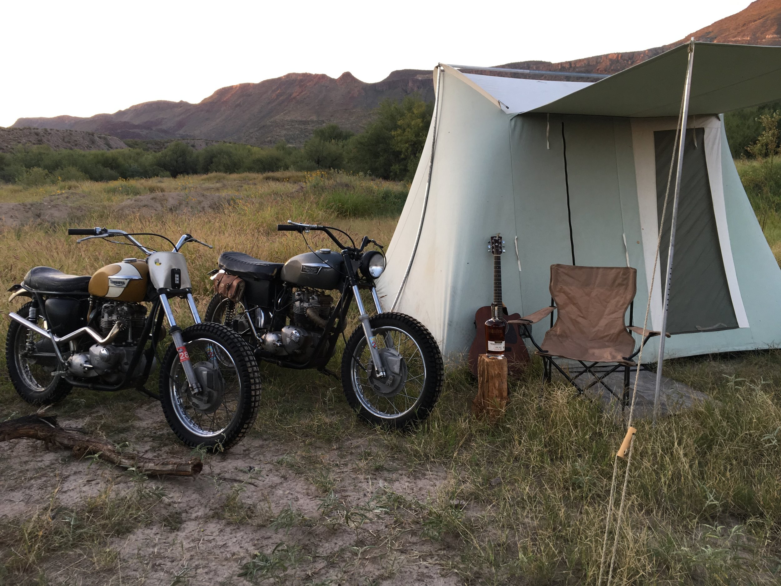 """My buddy Jake Hayhurst brought """"Frank"""" (short for Frankenstein,) a 1971 Bonneville frame with a 1973 750cc engine. Frank and Goldie seen here in front of Jake's tent, just hanging and dreaming about the desert."""