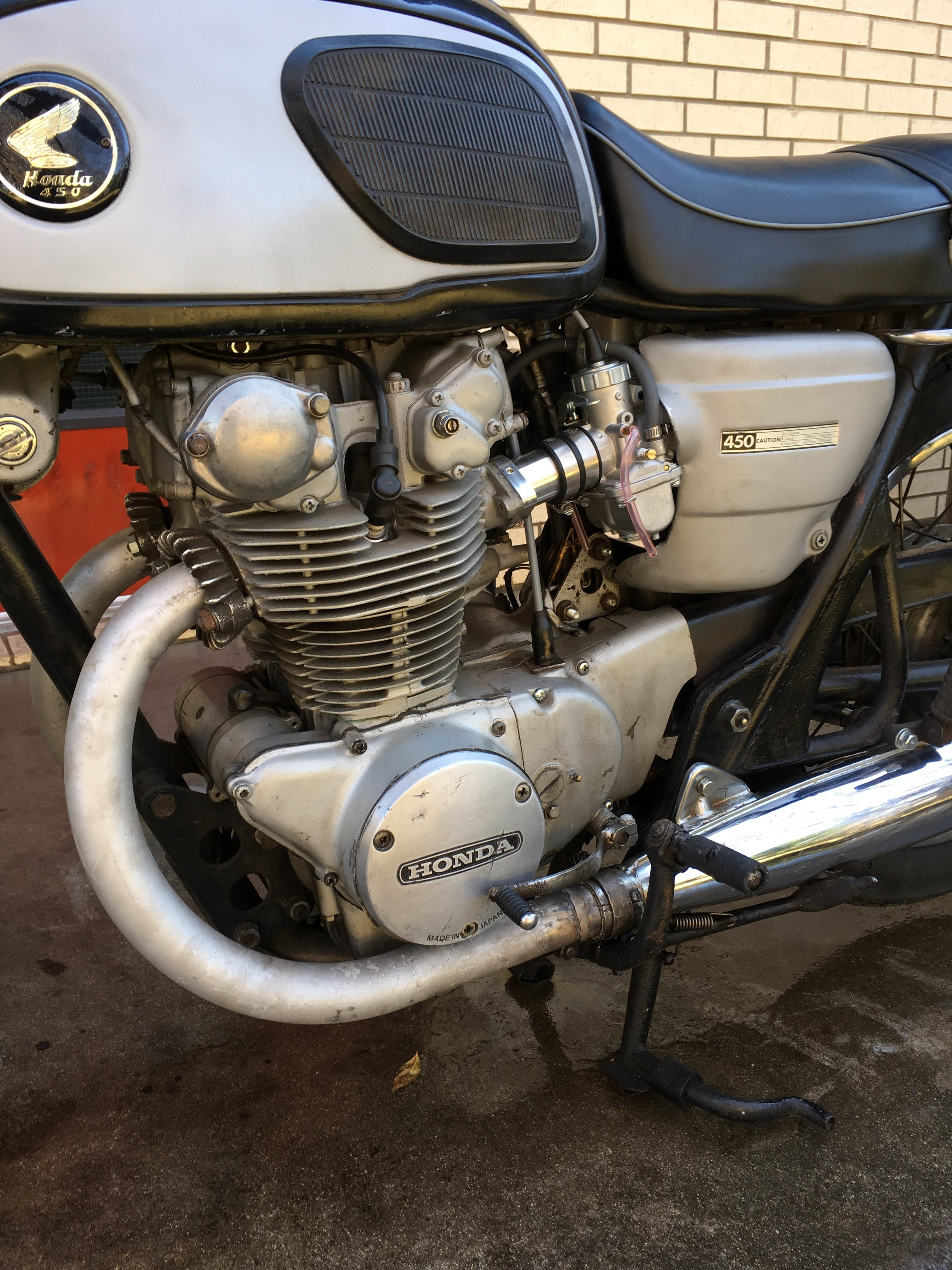 Still pretty rough. A lot of things could be done to make it more correct, but where do you stop? The owner was after a reliable rider, so the roughness allows you to ride with some abandon. The Mikuni 32mm carbs came from Dime City Cycles in a complete kit that had intakes, carbs, filters, and cables. A good bit of trimming was necessary to make the stock covers fit. The bike had an oozing dent in the magneto cover and the twisted shift pedal that went with it that was repaired by a used replacement cover and some heating and bending on the shifter.