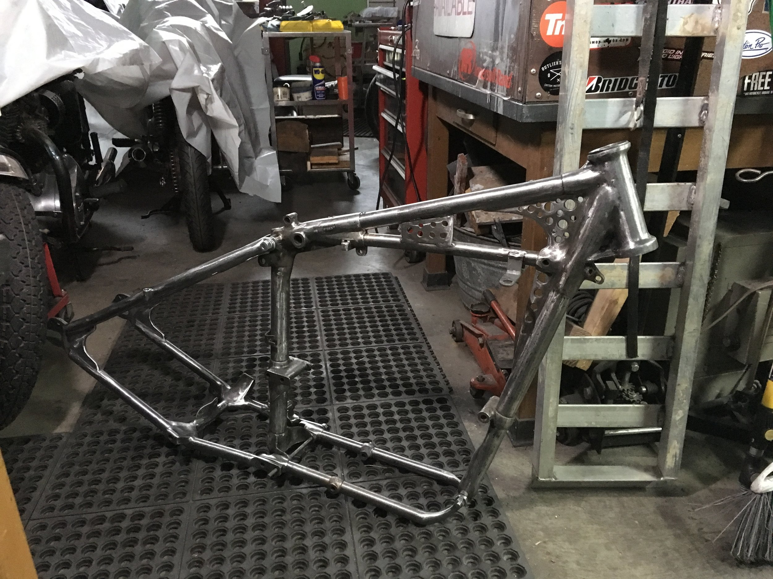 Putting together pieces of the 1957 Triumph Thunderbird frame for final metal finishing, Gouges, pitting, welding porosity and bad welds are being ground out and filled to get the frame smooth enough for chrome plating.