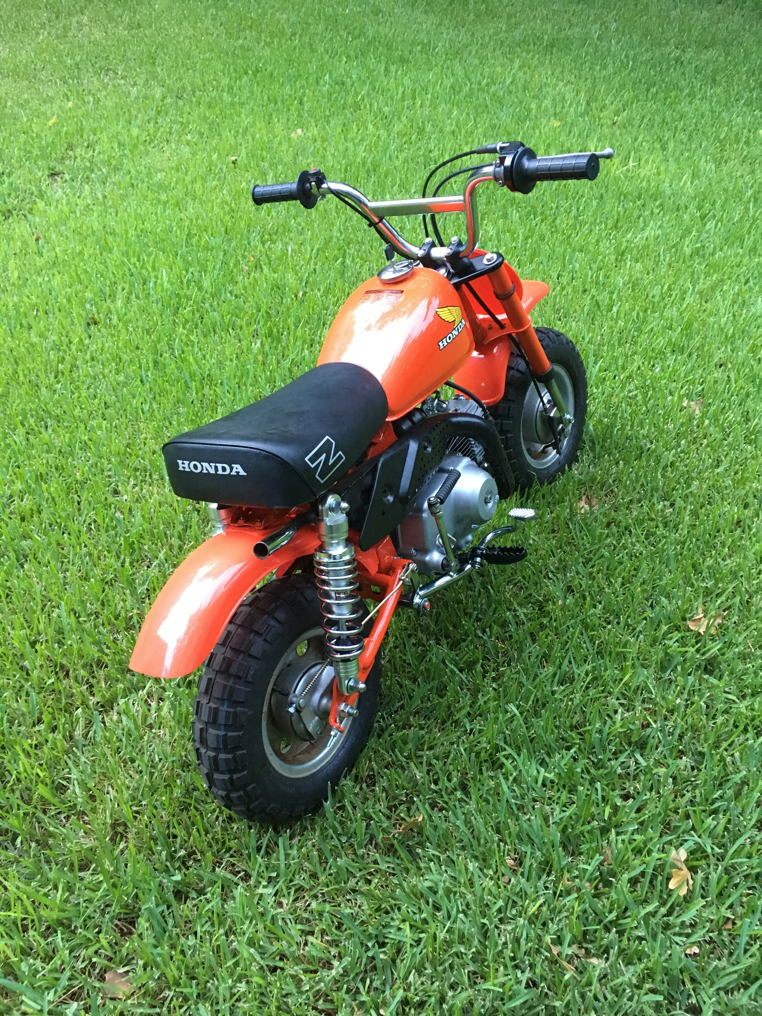 The 1979 is a transition year. The very first Z50R, but retaining some gear from the 1972-1978 early soft tails like the wheels and hubs, the rear brake pedal (painted black) and rod, and a similar muffler to the 72-78, leaving off the number plate on the right side that the later 1980-1987 Z50R models had. The muffler guard appears to be from a 1988-1999 model, but it is fine with the owner for now. The original seat would have had no logos on the sides, this one appears to be a repop. The bike took third place in the minibike category at the Land of the Pines rallye,