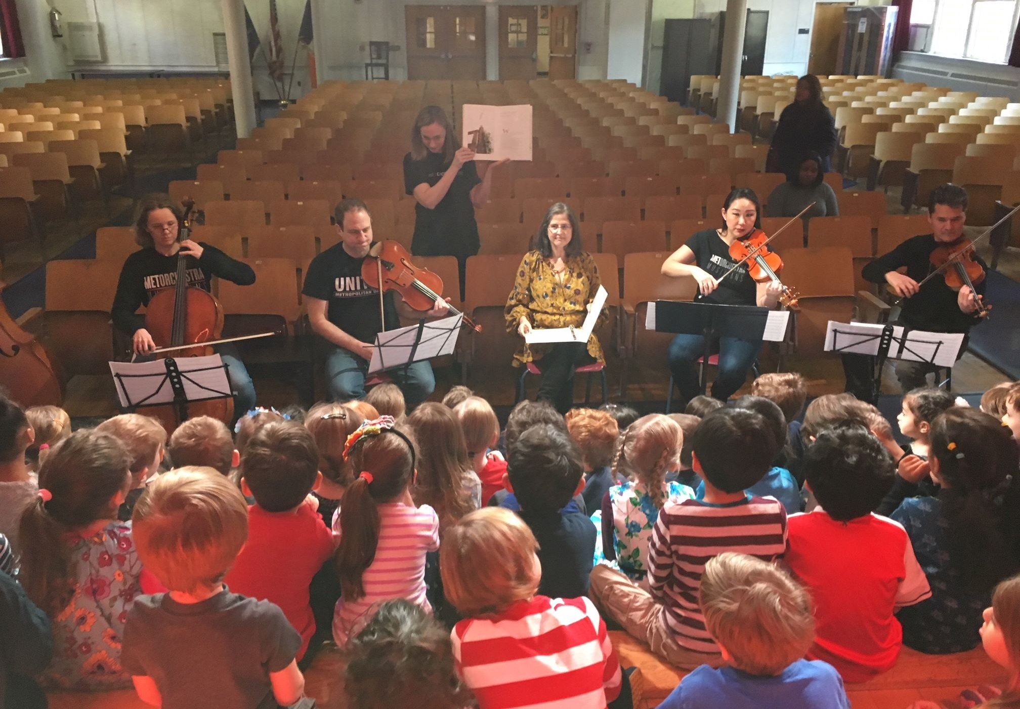 Met Chorister Karen Dixon, Met Orchestra Musicians Kari Docter, Dov Scheindlin, Katherine Fong, and Bruno Eicher, and NYC Council Member Helen Rosenthal enthralling a group of Kindergartners at PS 166.
