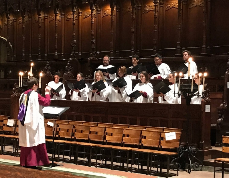 The professional choir of St. John the Divine during an Evensong service. Lianne Coble-Dispensa (front row, far right, in glasses, hiding behind the candelabra) and Scott Dispensa (second row, second from the left) are full-time members of the choir, on top of being full-time members of the Met Chorus.
