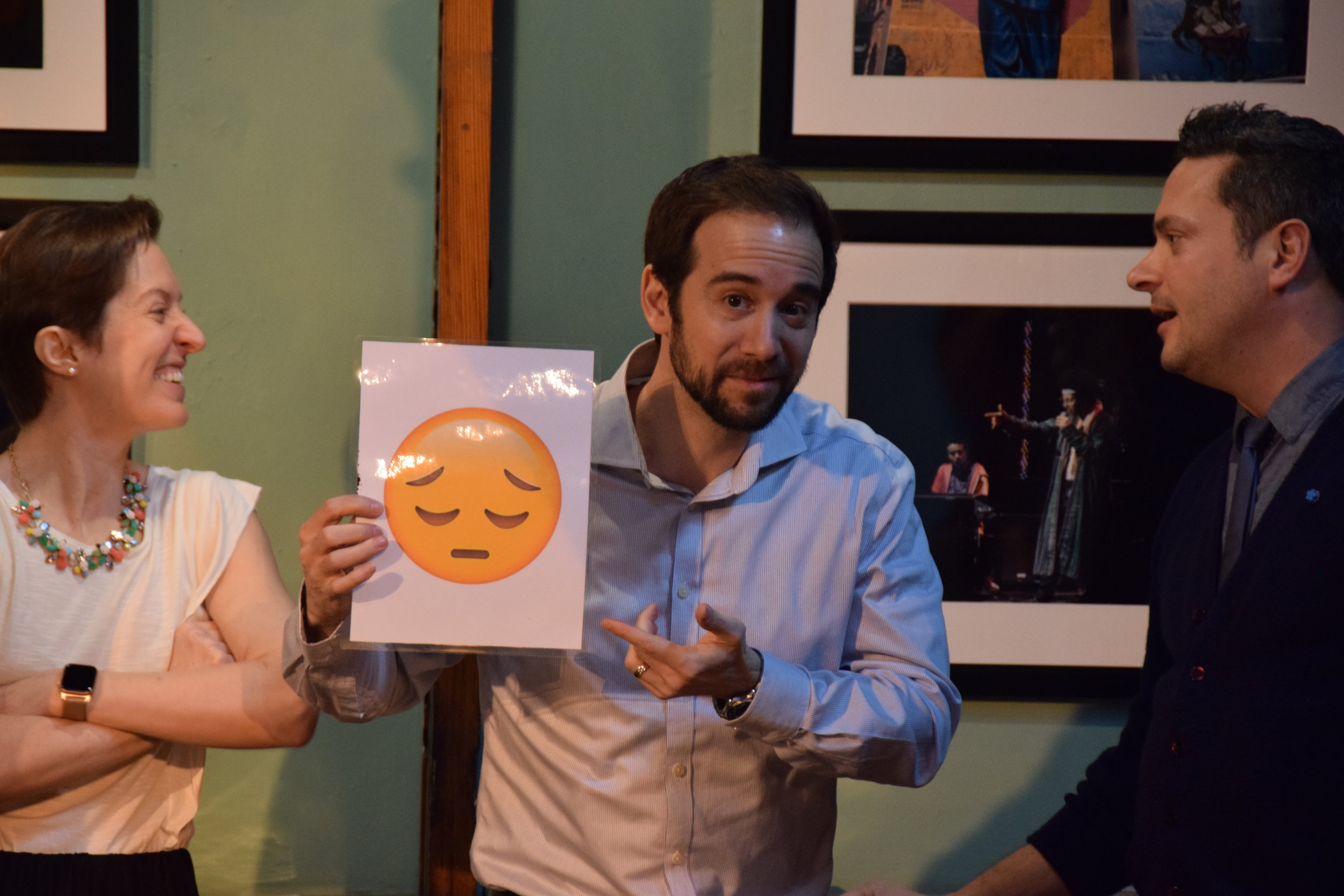 """Ross Benoliel, presenting a """"sad"""" emoji, with good-natured encouragement from Lianne Coble-Dispensa and Nathan Carlisle."""