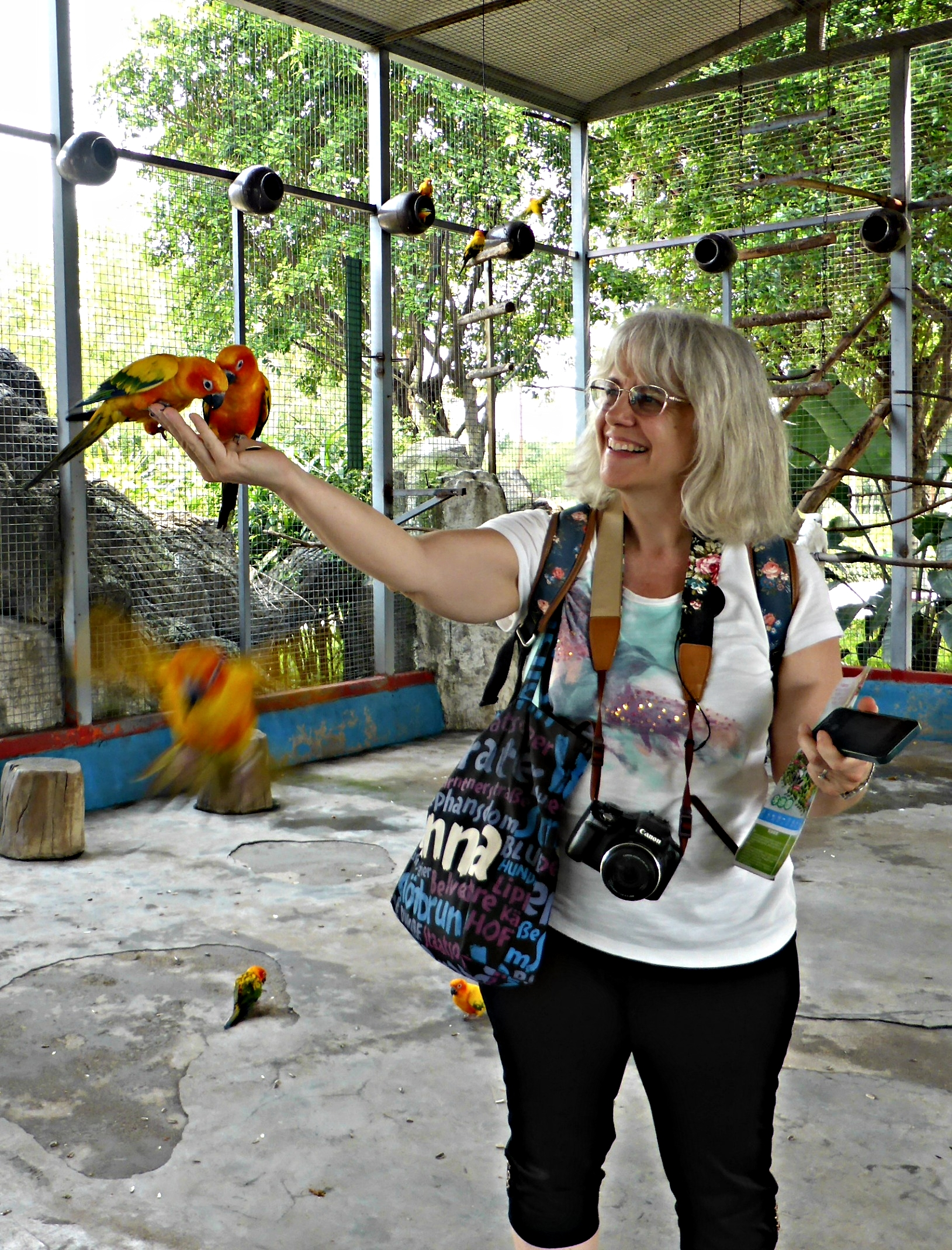 I hadn't paid to feed the parakeets, I just went in to take pictures, but the man working came and put some seeds in my hand so Leah took my picture :-)