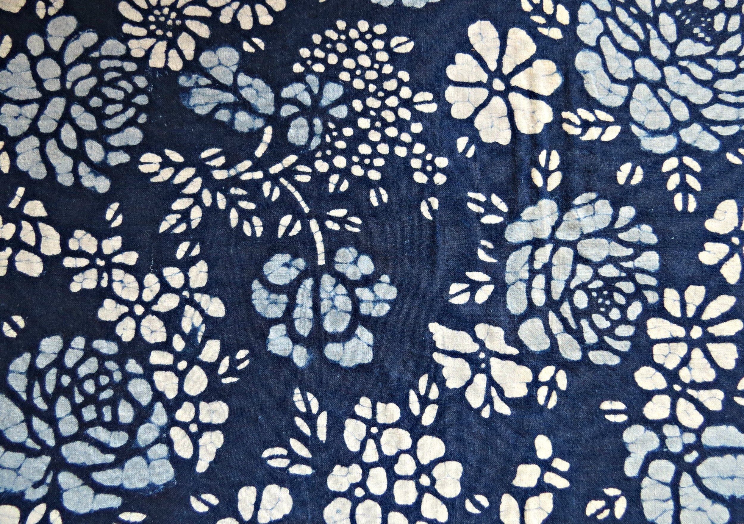 I have not actually been anywhere to see the Batik process, but I am almost certain that this piece is batik. You can tell by the small lines in the design, which is where the wax cracked and allowed some dye to penetrate the cloth. This is also a good example of the two tones of blue sometimes seen.