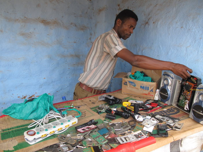 Ali Daud Omar will repair your cell phone for $6. He's one of the refugees benefiting from the Ugandan government's right to work policy.   Gregory Warner/NPR