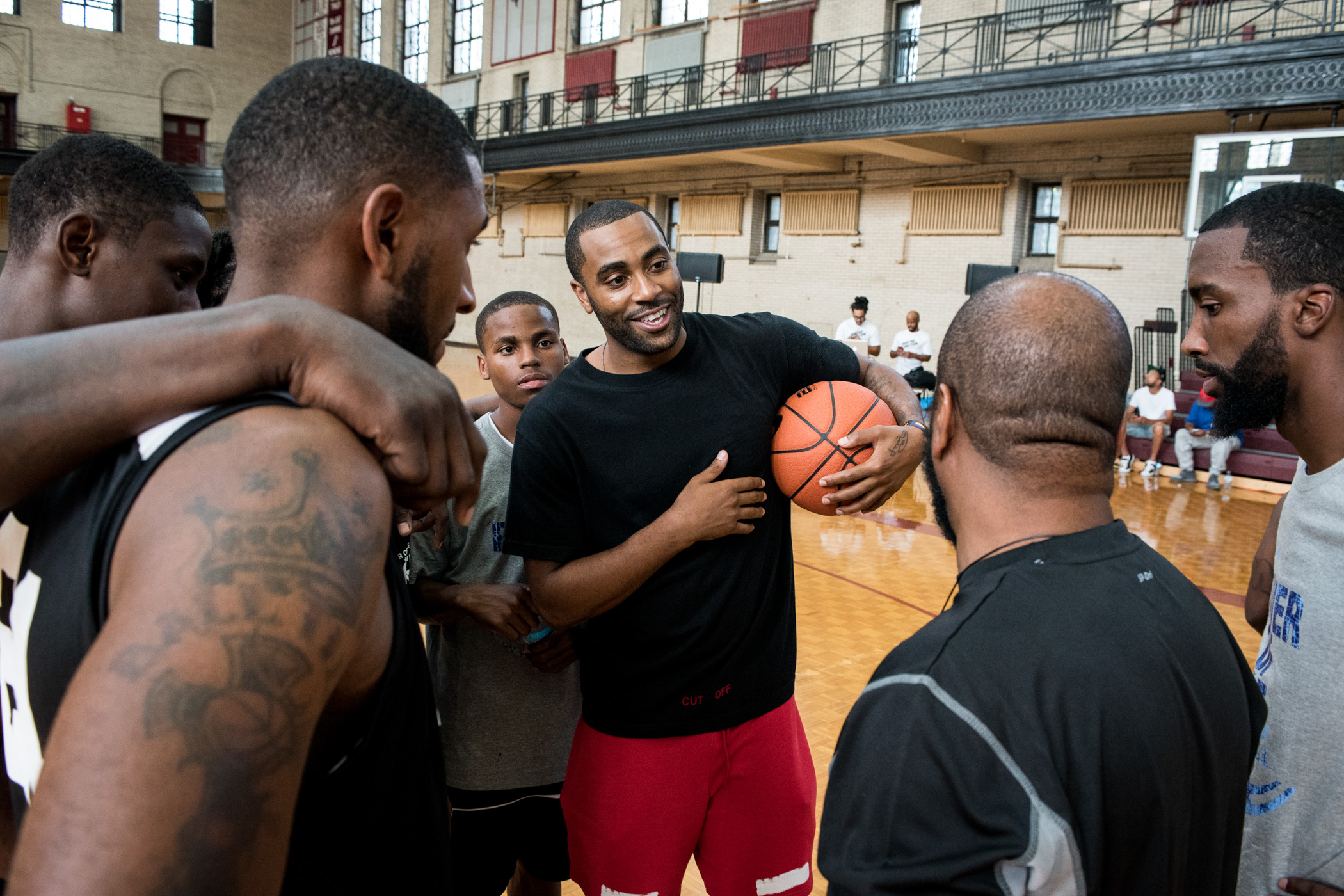 NBA player Wayne Ellington Jr. of the Miami Heat, center, speaks to team Philadelphia No. 2 before its finals matchup against Camden, NJ during the first annual Philadelphia Peace Games tournament inside the Girard College Gymnasium in Philadelphia on Saturday, Aug. 20, 2016. Ellington Jr. is a Philadelphia native who lost his father, Wayne Ellington Sr., on Nov. 9, 2014 to gun violence on the 5200 block of Marion Street in Philadelphia's Germantown neighborhood. Since then Ellington Jr. has been an outspoken athlete about the violence going on in his city and across the nation. (Michael Ares for ESPN)