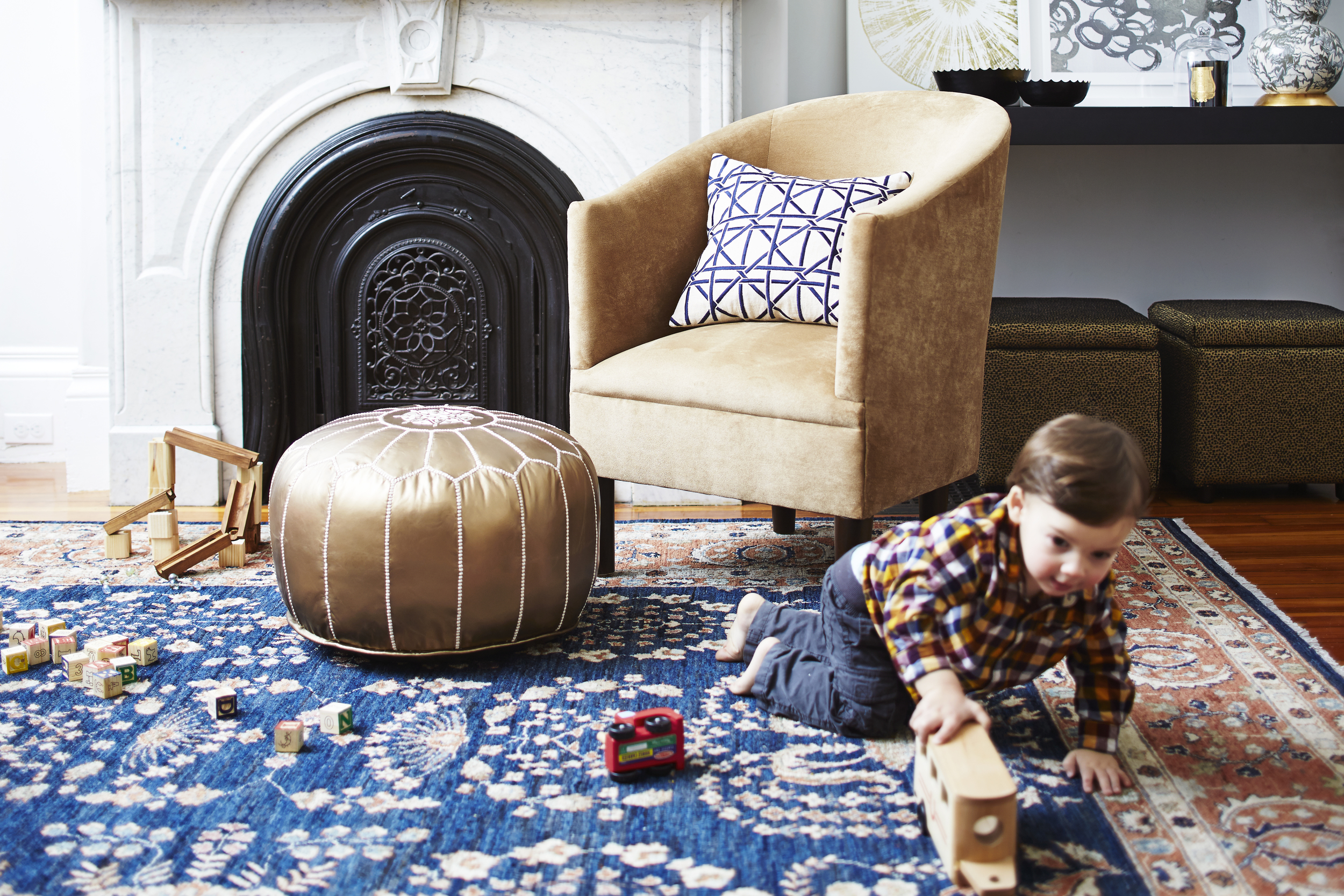 Don't mind the little cutie pie in front.  Rug, vintage from  Brimfield ; velvet tub chair,  Joss & Main ;bronze leather Moroccan pouf,  Wayfair ; accent pillow, Joss & Main; lamp,  Wayfair ; bowls, Wayfair .