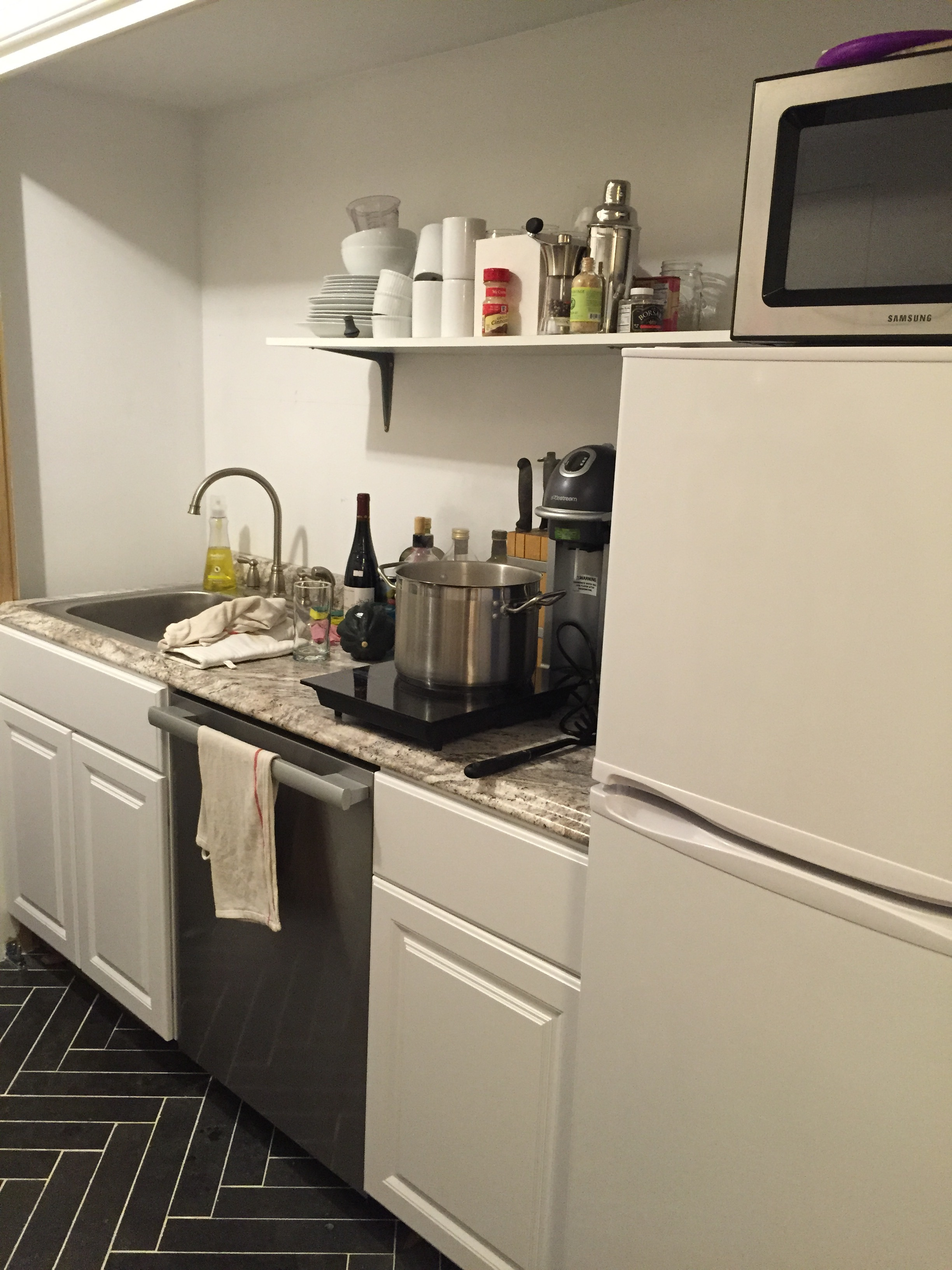 "Our ""crazy kitchen,"" as the kids called it, made from the cheapest Home Depot cabinets and counters we could get, the old sink and faucet from our previous kitchen, a compact Craigslist fridge, and a $100 convection toaster oven. It occupies what will eventually become our mudroom on the garden level. My husband installed it in three days, because apparently men from Ohio just know how to do things like that."