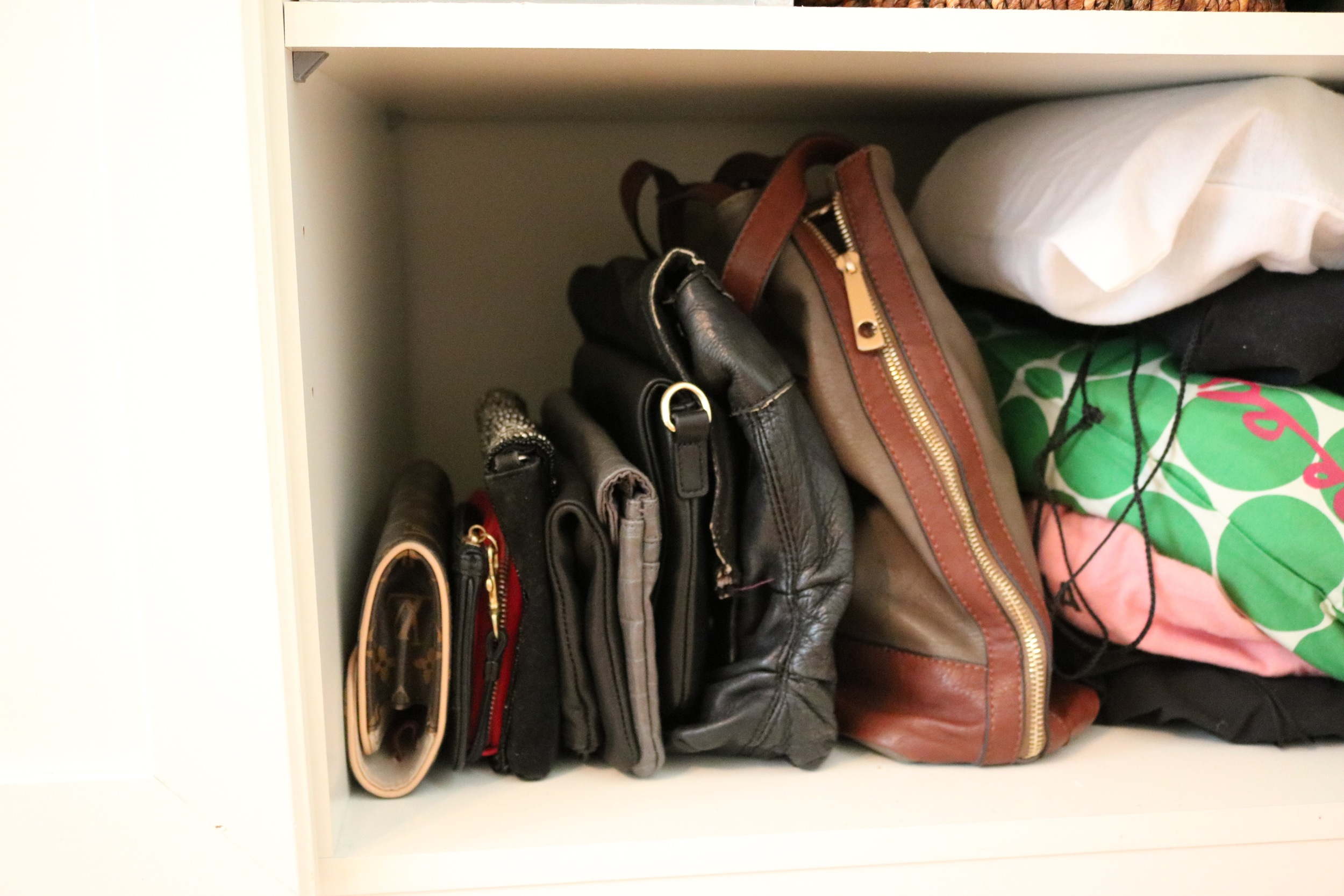 Handbags and clutches are stacked so I can easily identify each one in profile (or by its protective dust cover).