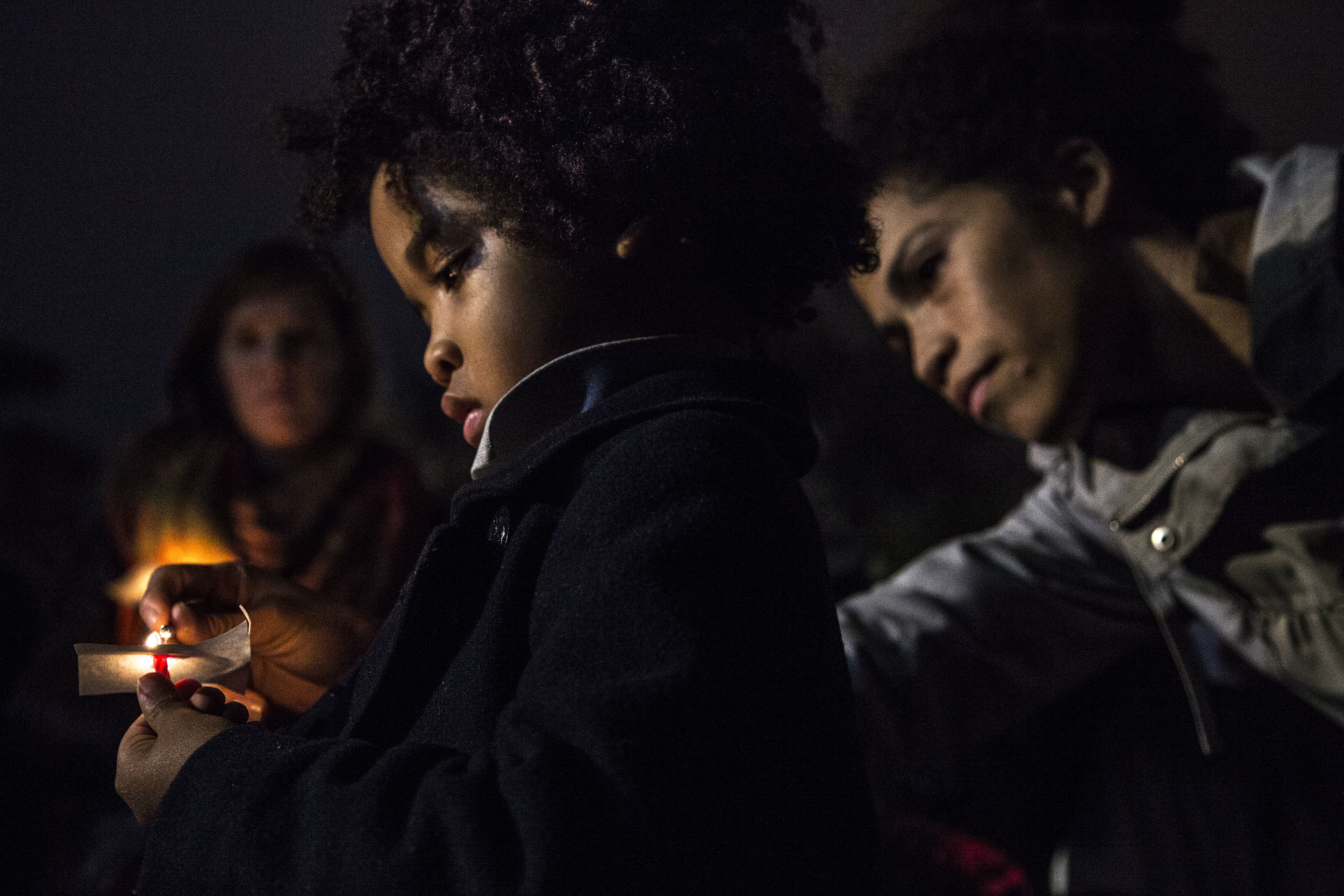 A mother lights the candle of her son during a candlelight vigil outside the White House, the evening after the 2016 presidential election.