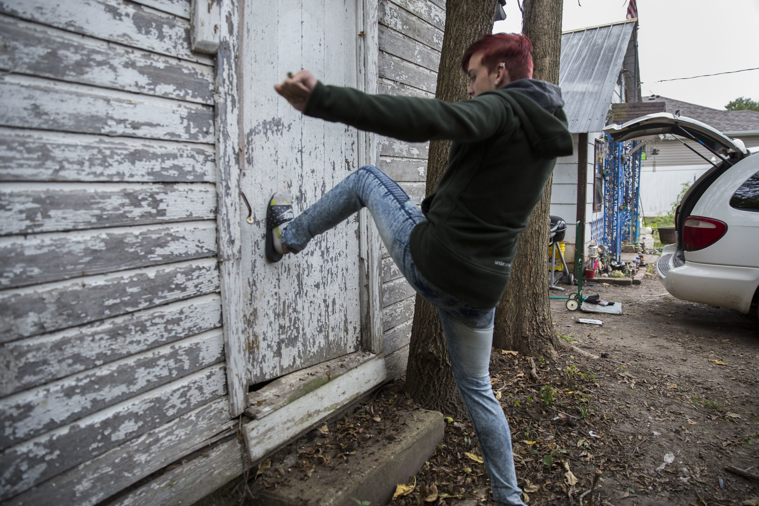 Billy kicks the door of an abandoned house next to Chris' home. These houses are often used by addicts as shelter to get high in.