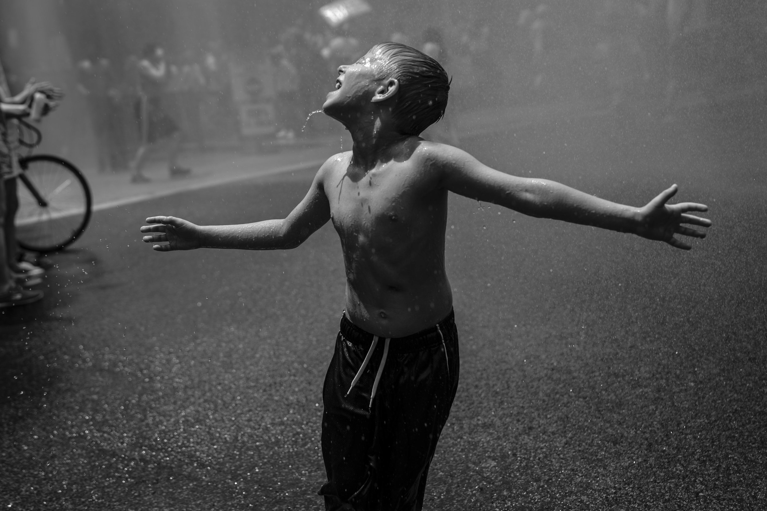 A boy cools off in water sprayed from a fire truck during a protest against the Trump administration's policy on separating immigrant families.