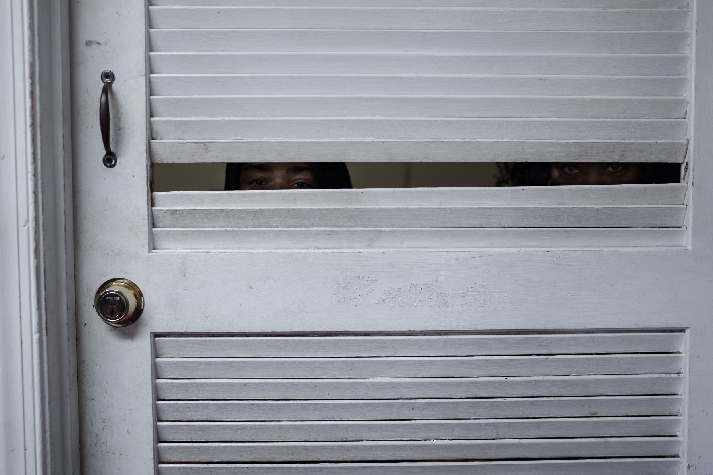 A young girl and a woman look through a door at a barber shop in Fredericksburg, VA.