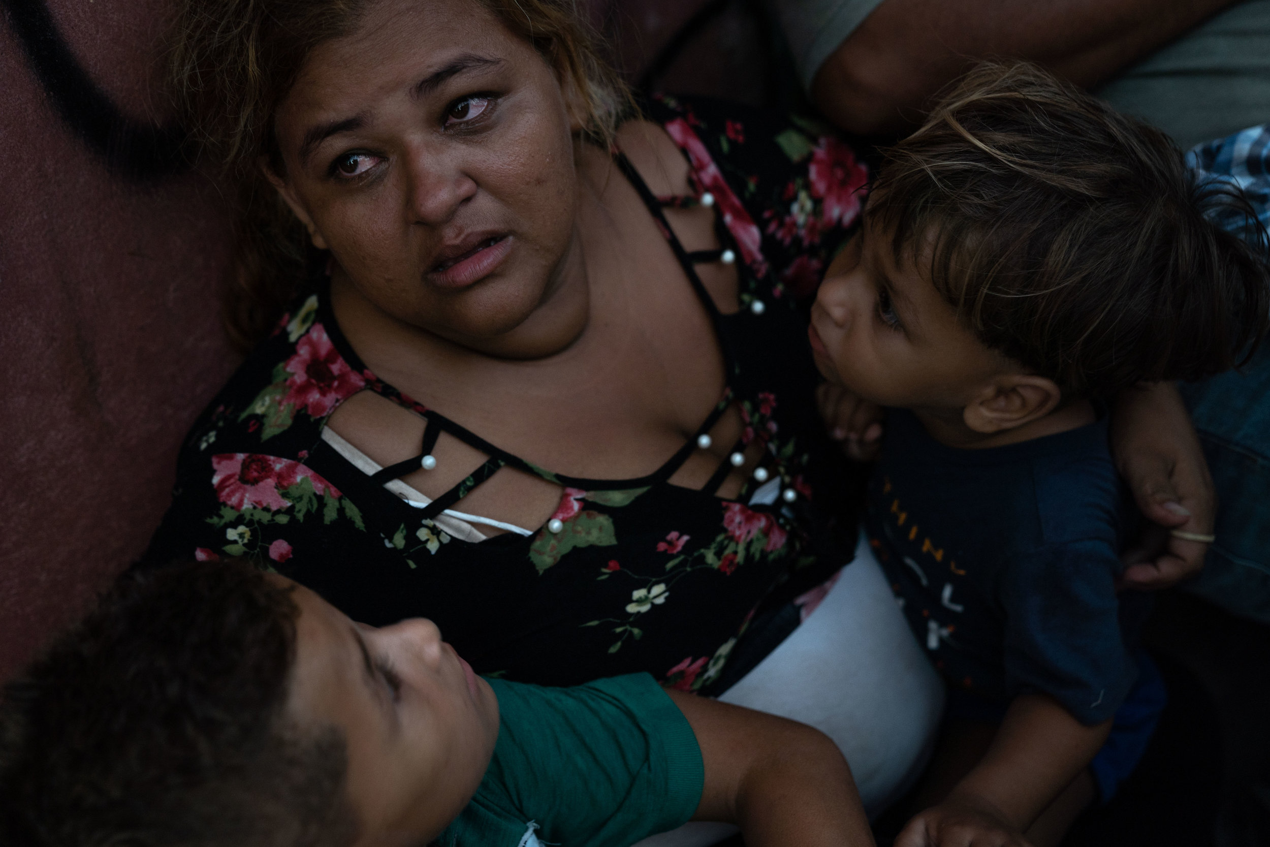 A Honduran migrant and her sons sit on a sidewalk, where they are sleeping due to shelters being over capacity in Tapachula, Mexico in June, 2019.