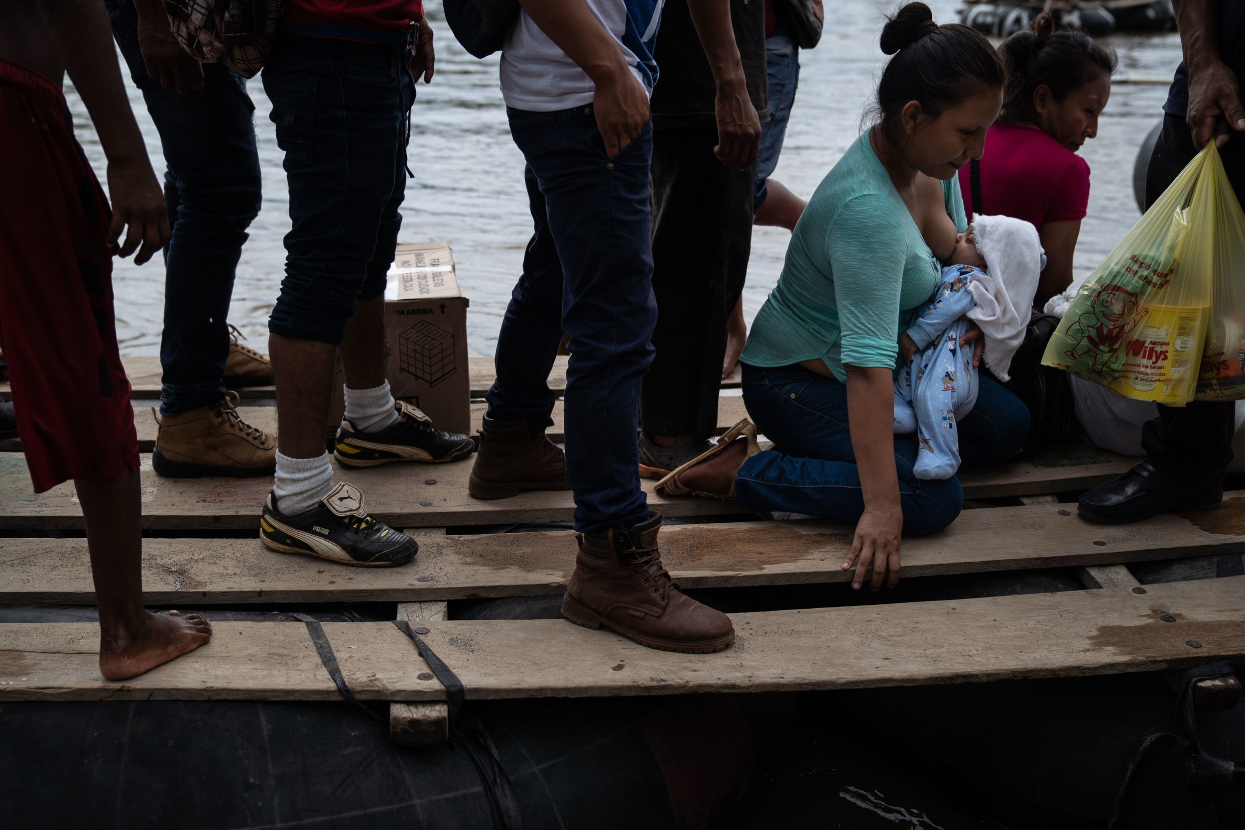 A woman breastfeeding her child crosses the Suchiate River at the Guatemala-Mexico border on a makeshift raft in August, 2018.