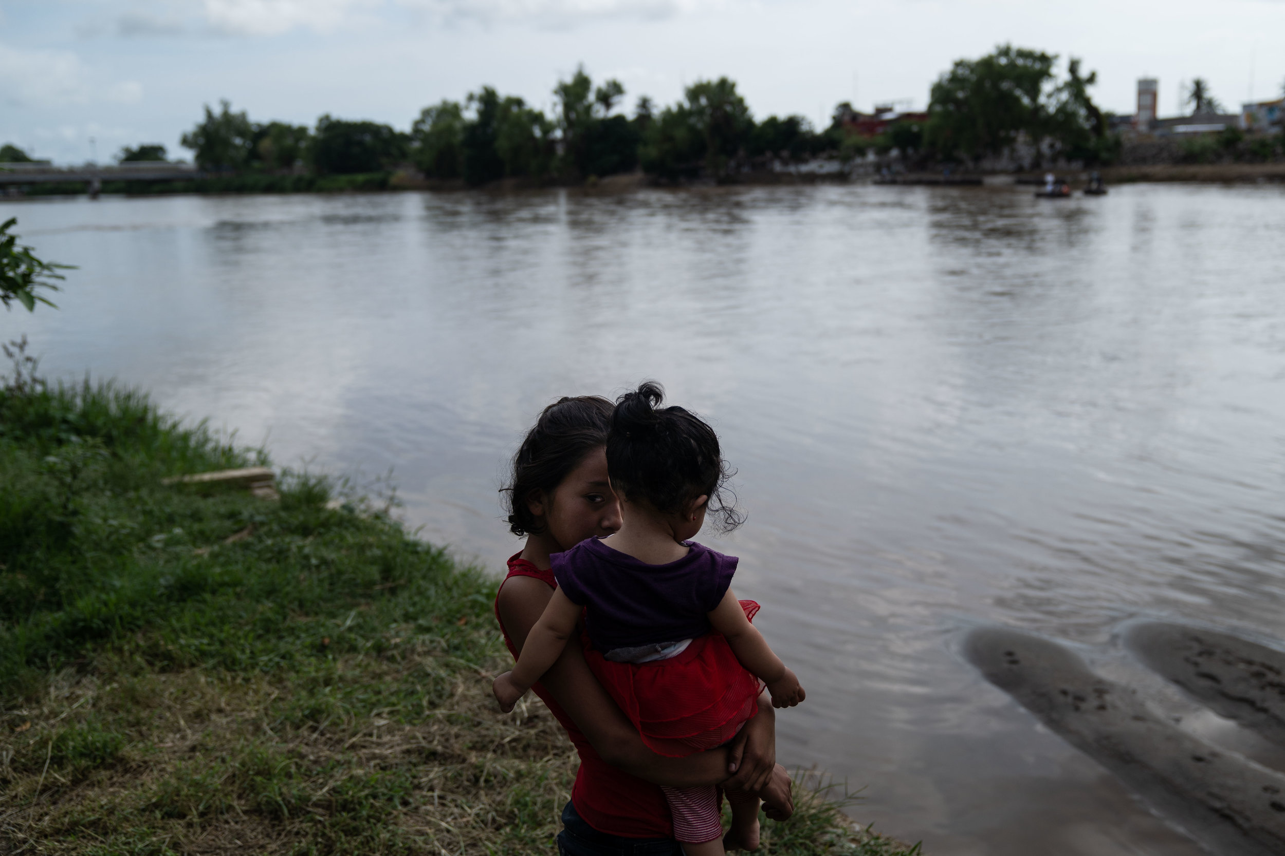 A woman and child stand next to the Suchiate river in Tecún Umán, Guatemala, 2018.